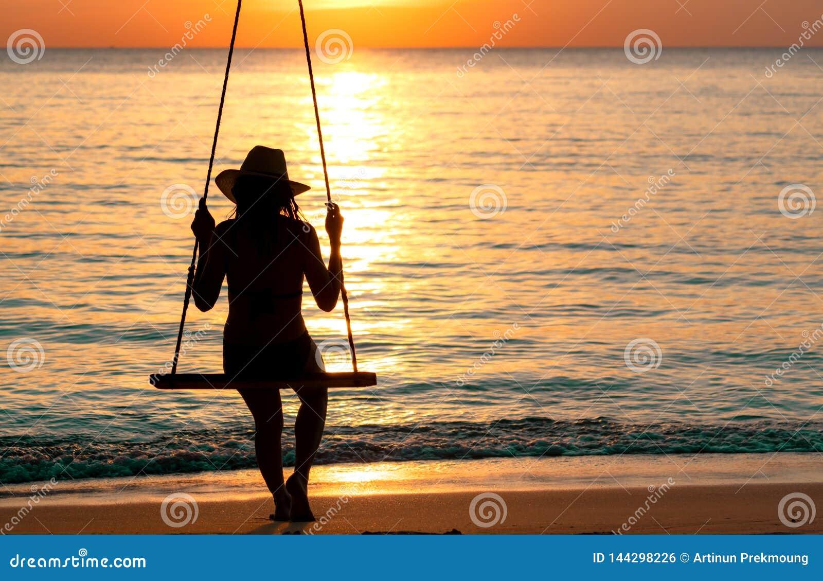 Schattenbildfrauenabnutzungsbikini- und -strohhutschwingen das Schwingen am Strand auf Sommerferien bei Sonnenuntergang Genießen