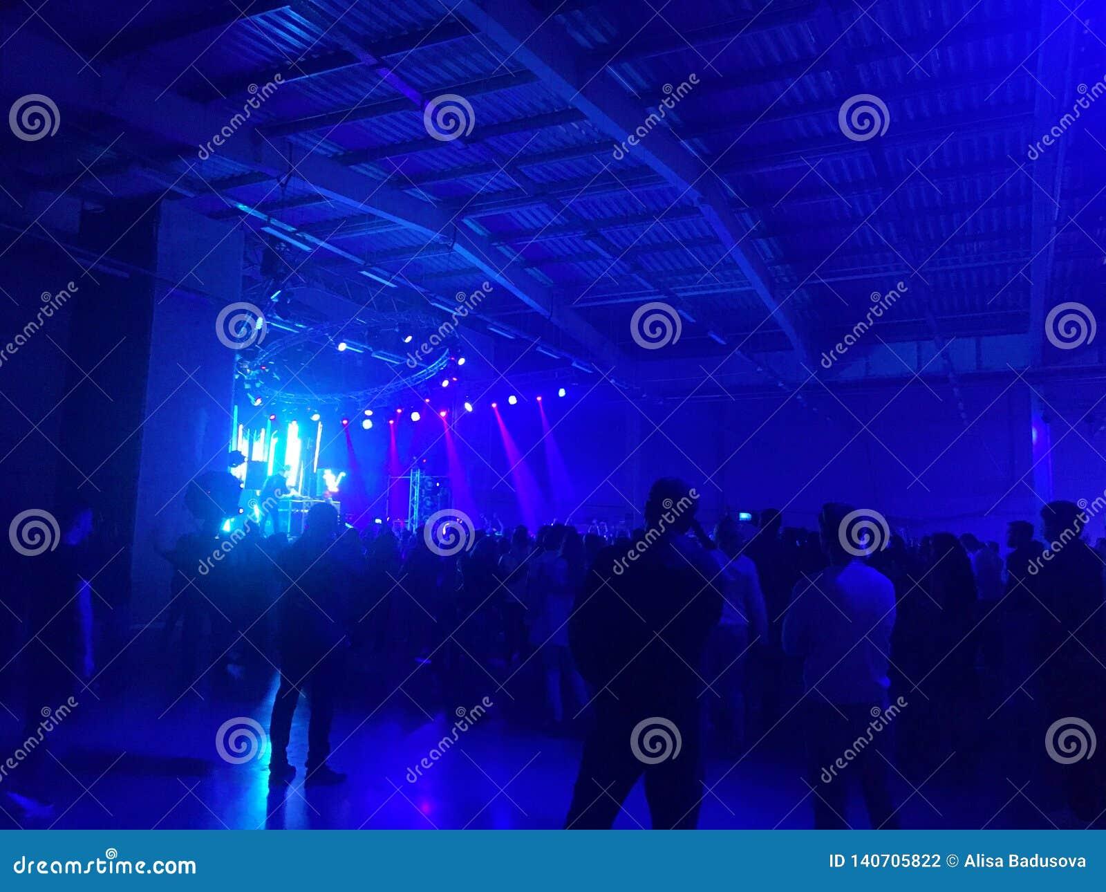Schattenbildhände von den Publikumsmengenleuten benutzen intelligente Telefone die Vereinpartei mit Konzert genießend