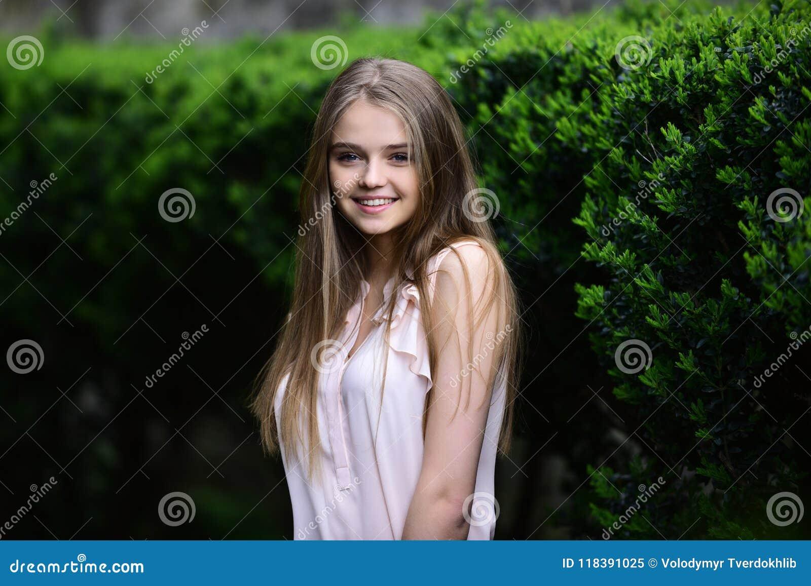 Schauen Sie vom Mädchen nahe Grünpflanzen Sommer oder Frühlingsmode und -schönheit Mädchen in der zufälligen Kleidung im Freien S