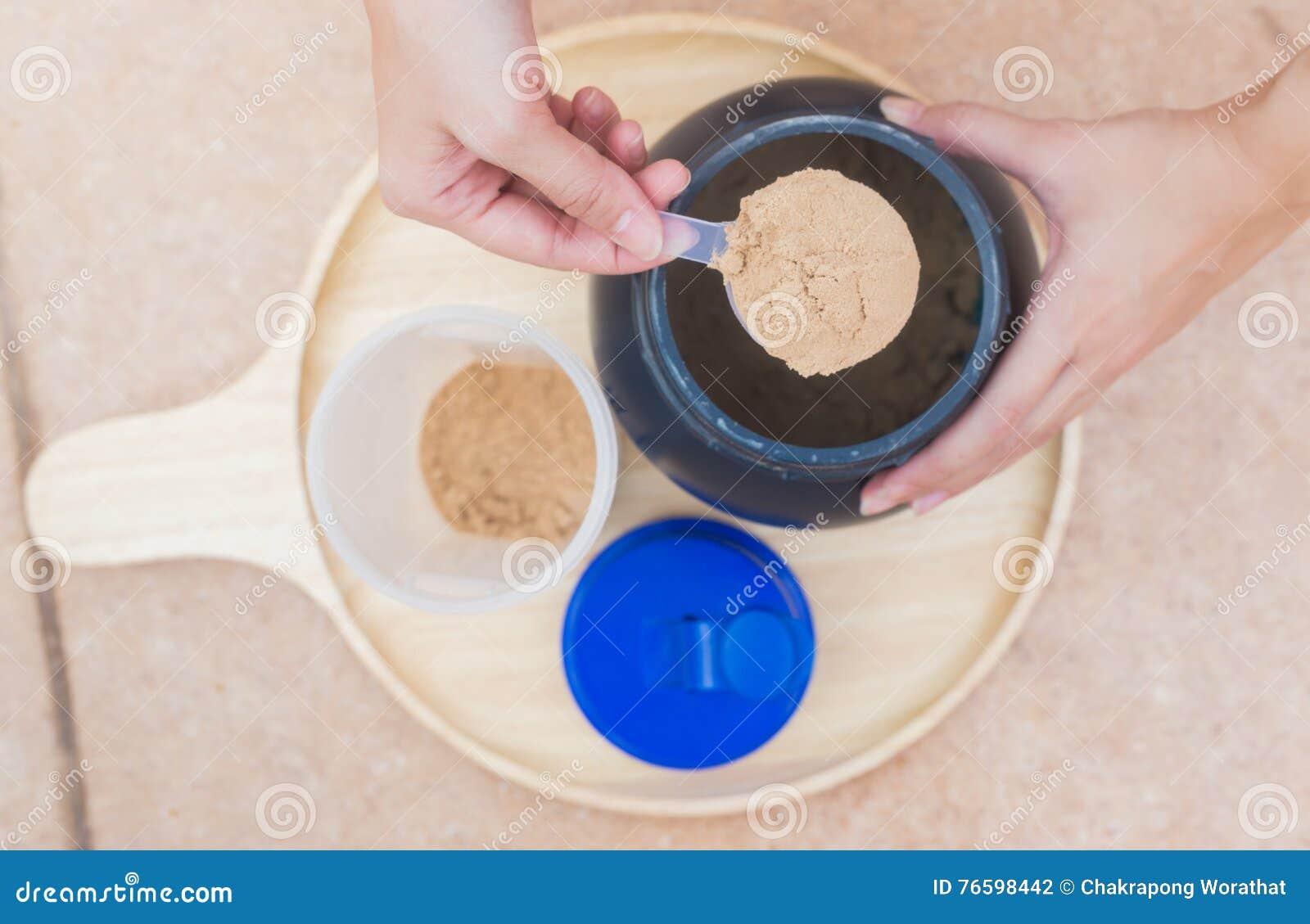 Schaufel des Molkeproteins auf einer hölzernen Platte mit Glas