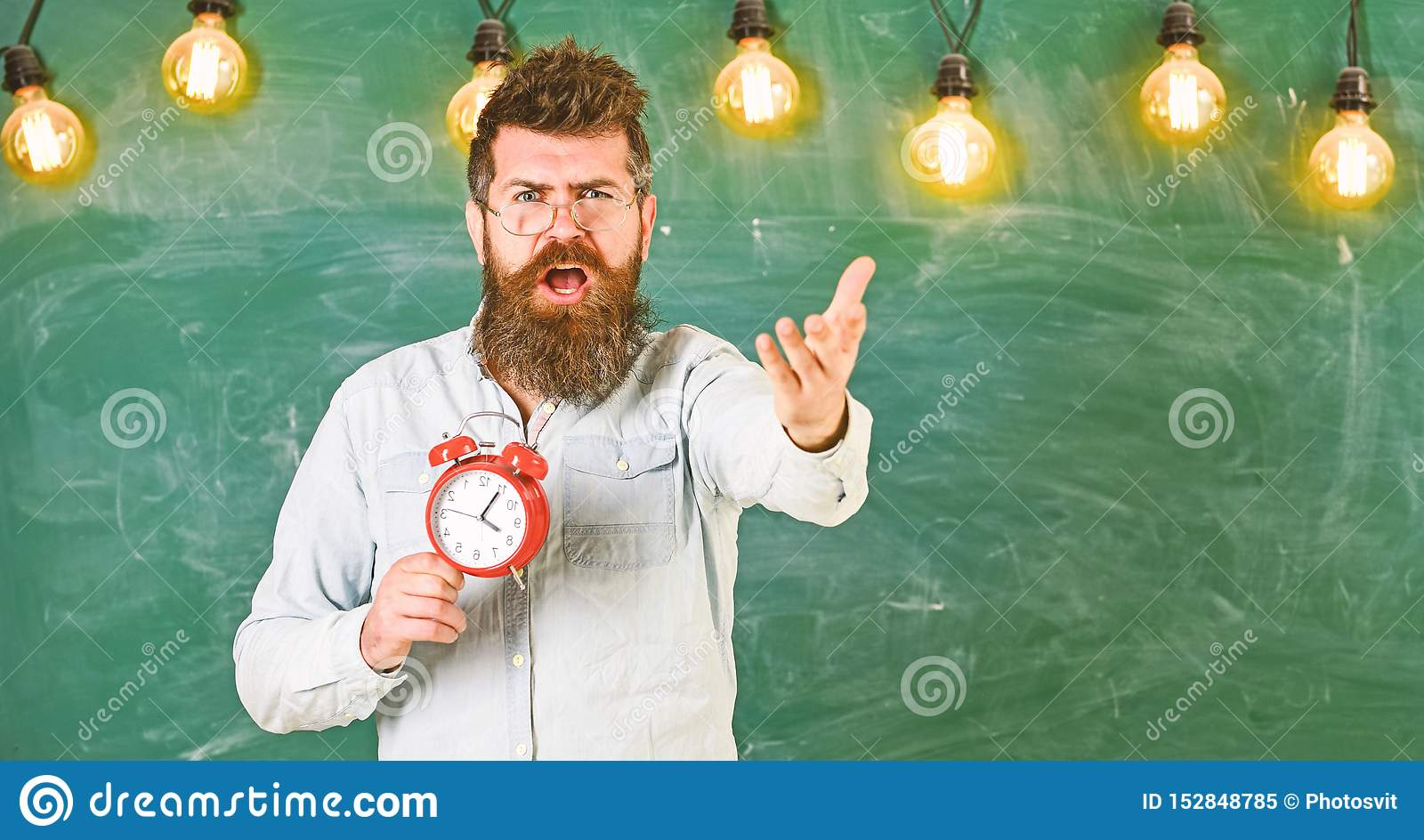 Schedule and regime concept. Bearded hipster holds clock, chalkboard on background, copy space. Man with beard on