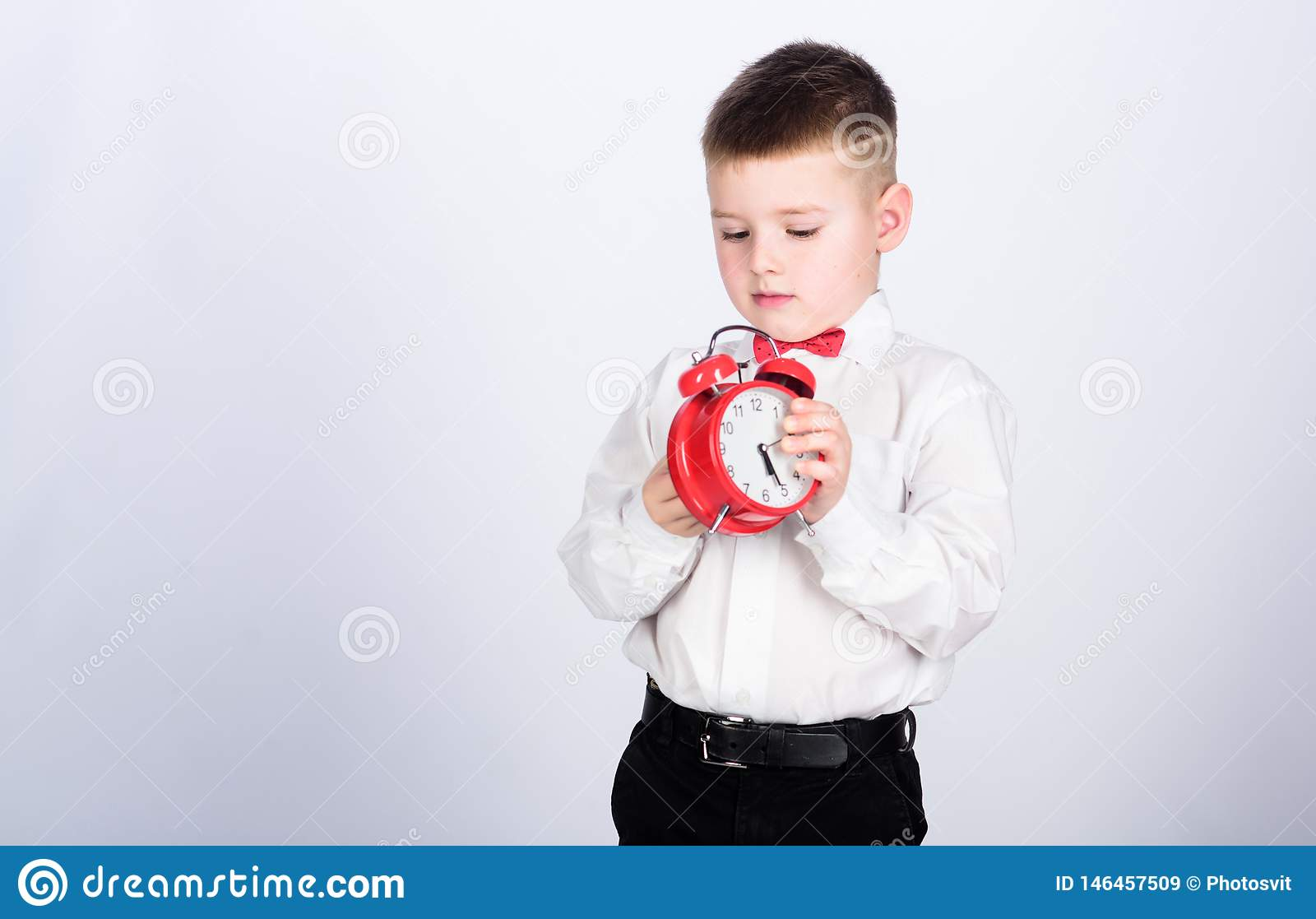 Schedule and timing. Morning routine. Schoolboy with alarm clock. Kid adorable boy white shirt red bow tie. Develop self