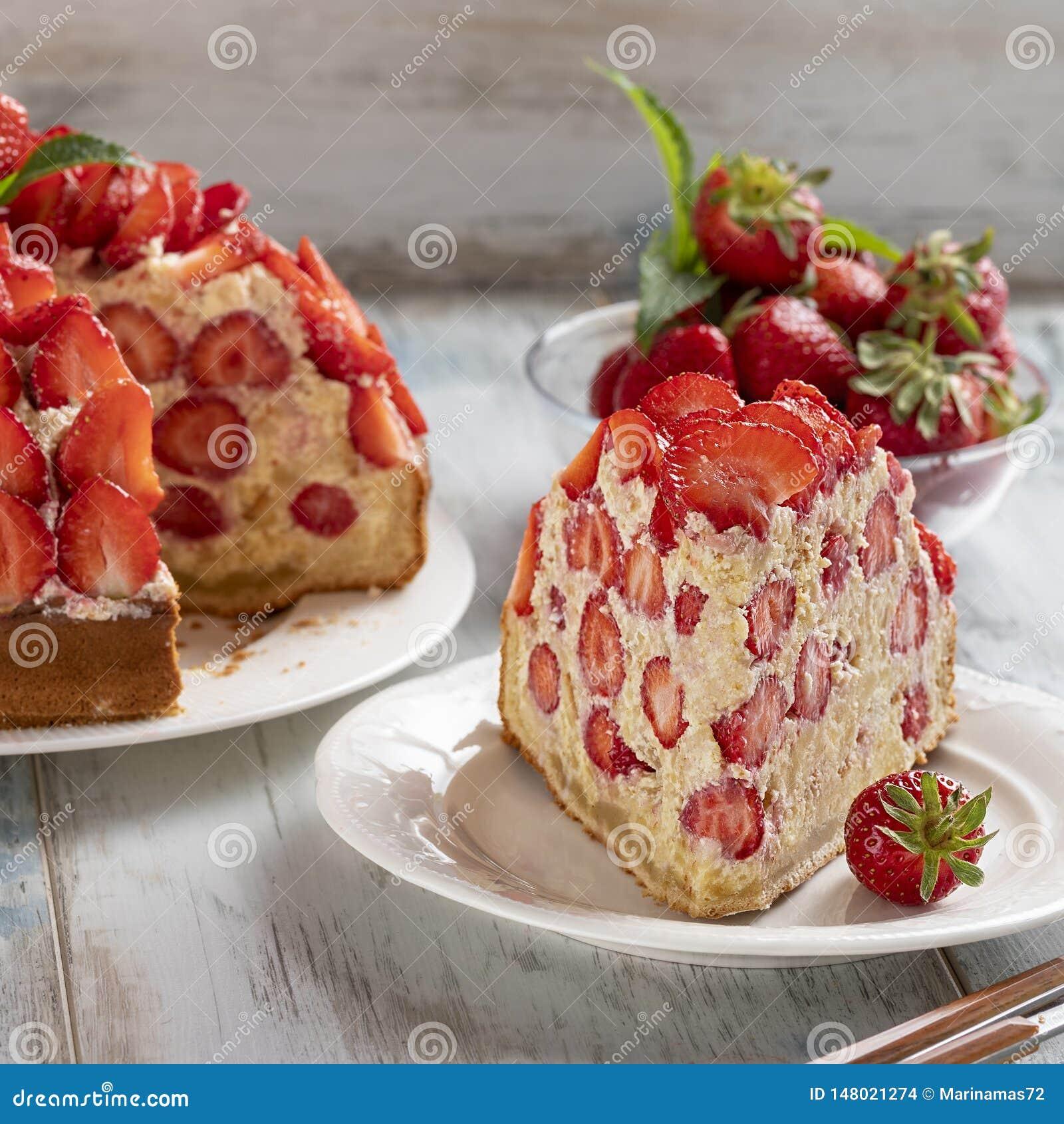 Scheibe des Erdbeerkuchens mit Vanillecreme verzierte mit frischen Erdbeeren und Minze
