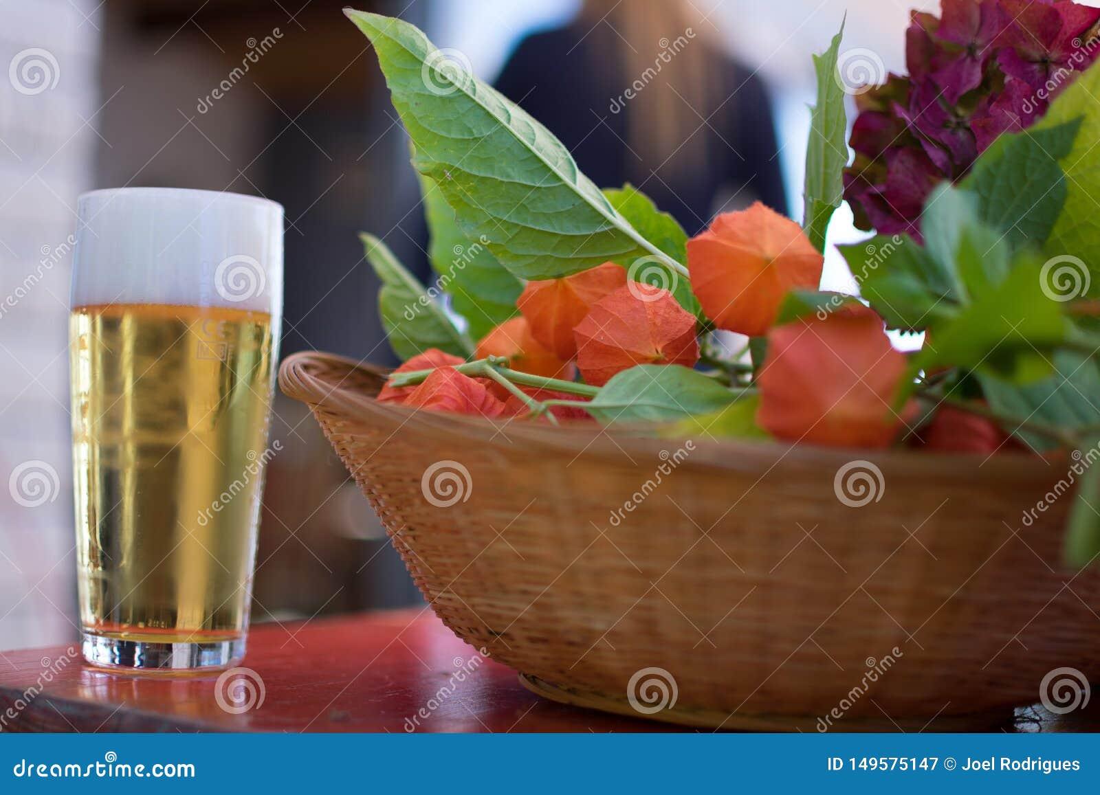 Scheidel, Luxemburg - September 8 2018: Vers glas bier naast een mand met physalisfruit