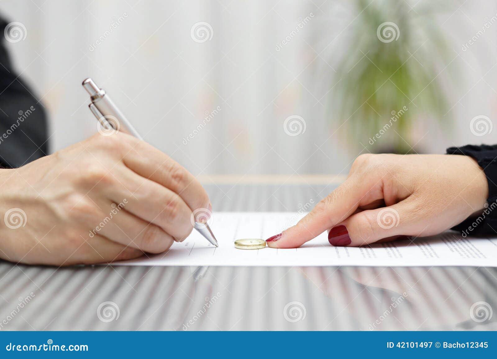 Scheidungsvereinbarung und -frau des Ehemanns drücken unterzeichnende Ring weg