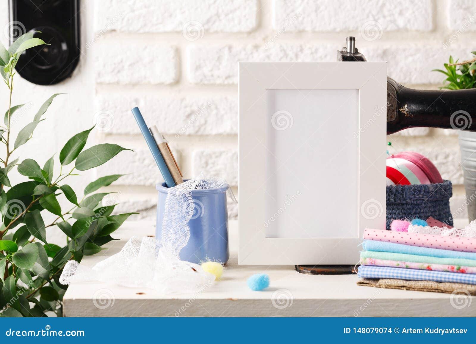 Scheinoben weißer Rahmen auf dem weißen Backsteinmauerhintergrund, den Nähmaschinen der Weinlese und den Stapeln von Geweben Mode