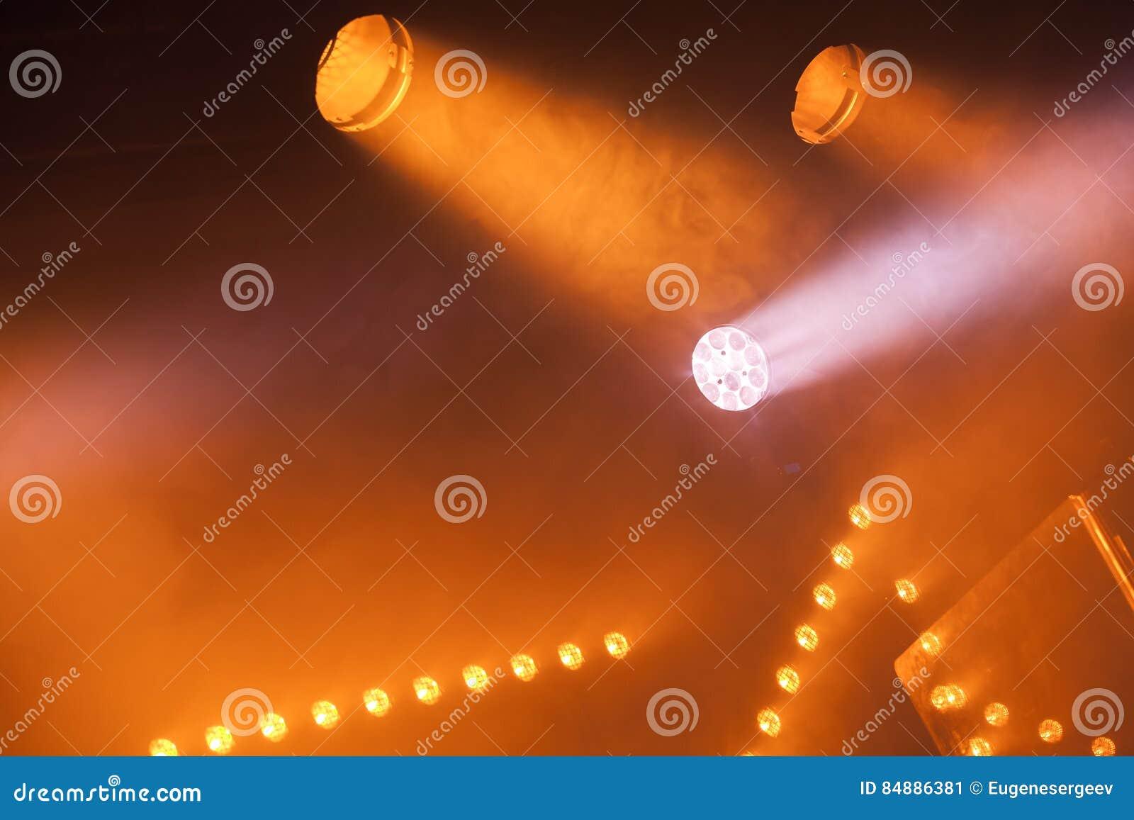 Scheinwerferlichter mit gelben Strahlen im Rauche