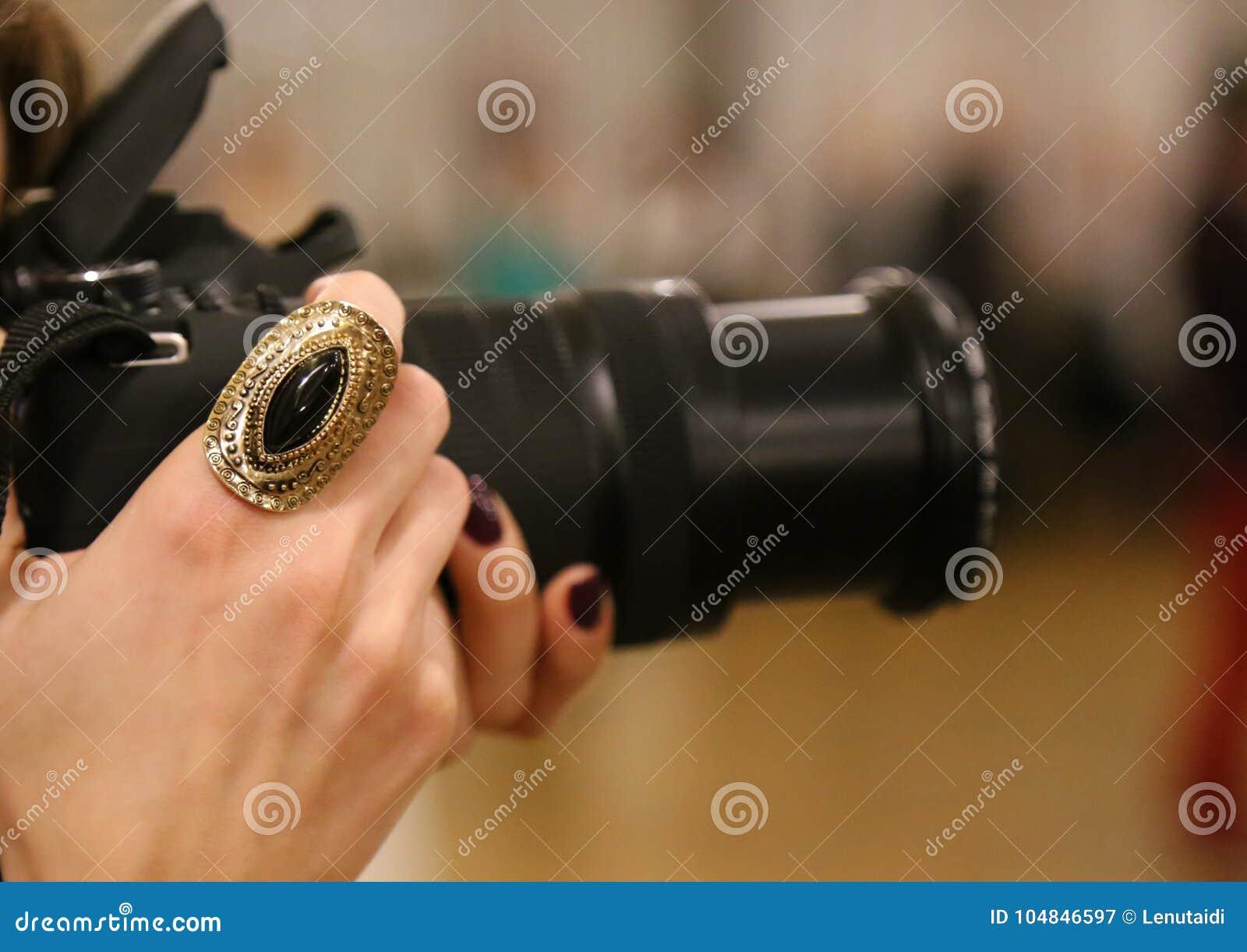 Schellen Sie auf der Hand eines weiblichen Fotografen