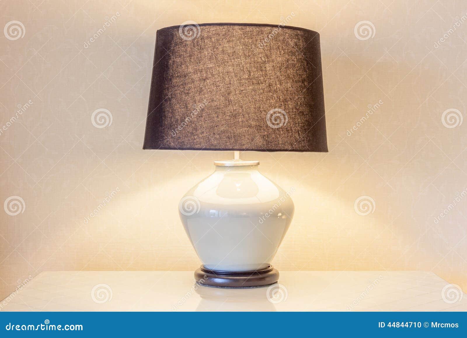 Schemerlamp en zijn schaduw op behang in de slaapkamer stock foto