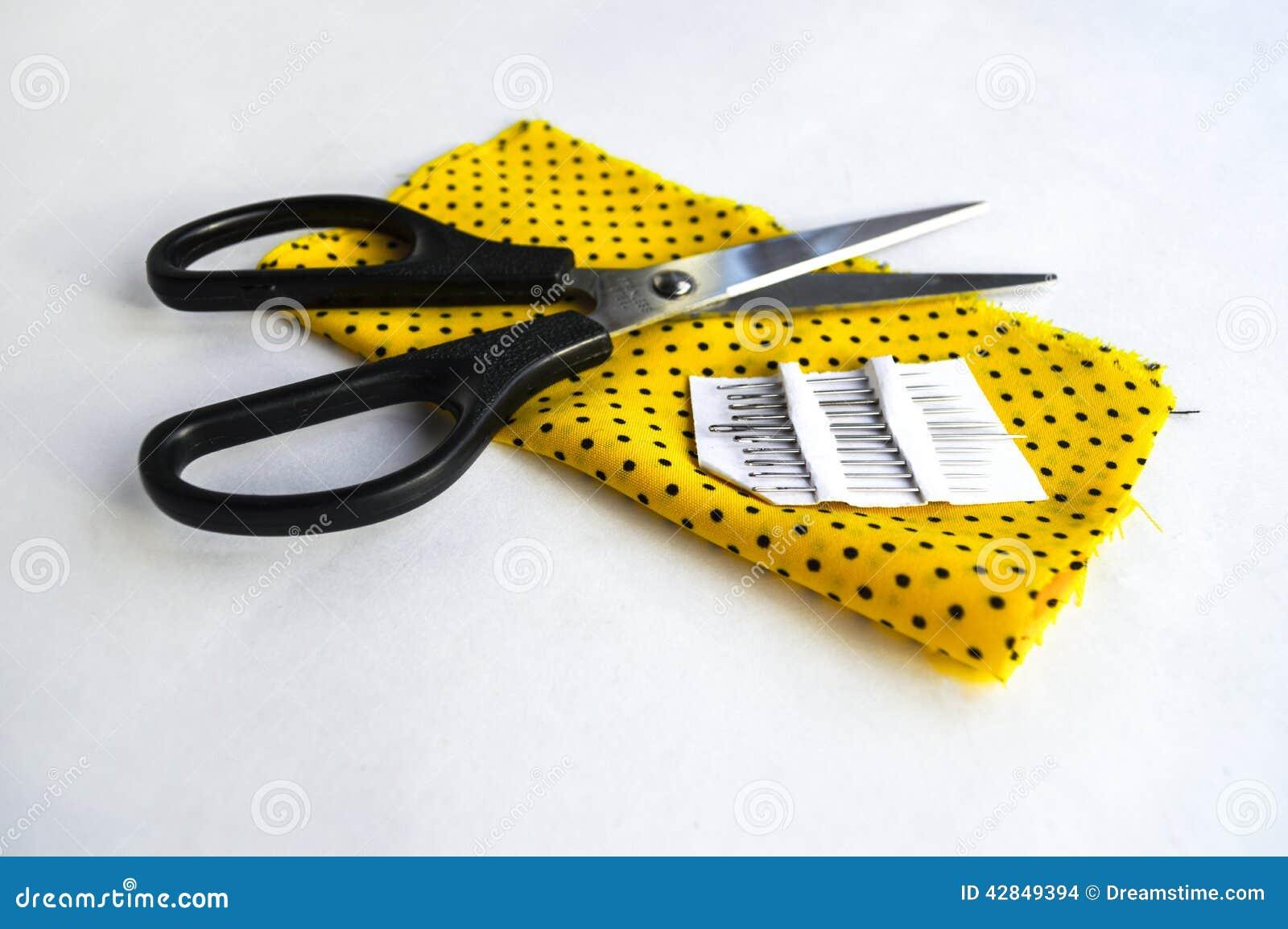 Scheren und Nadel auf gelbem Stoff