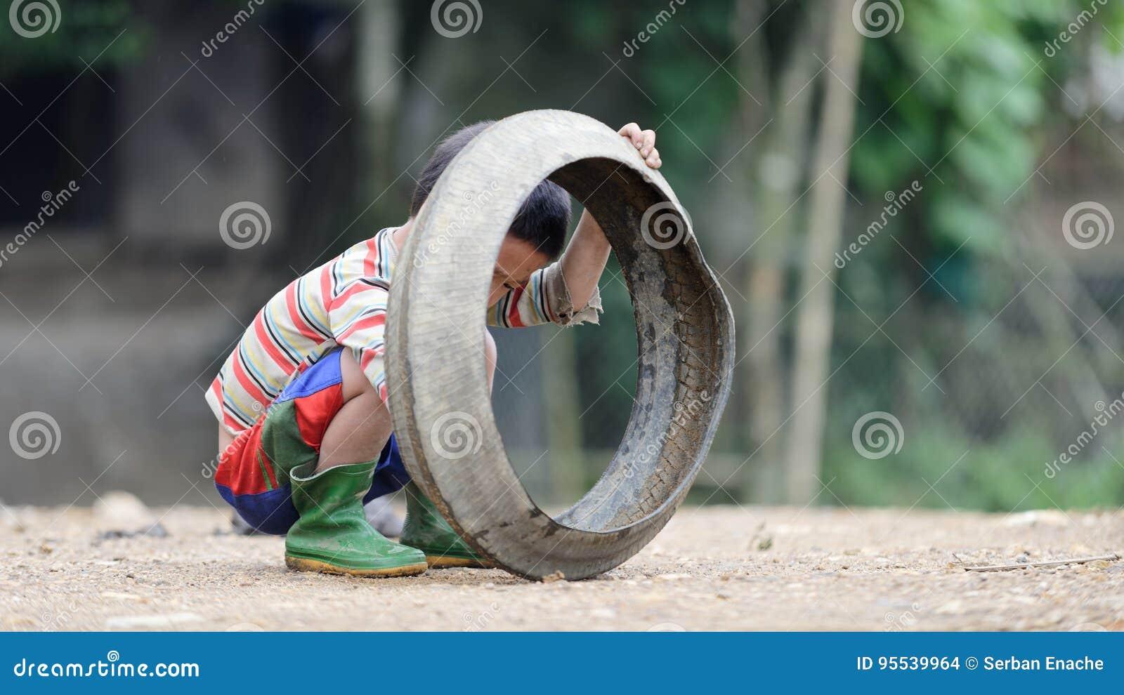 Scherzen Sie das Spielen mit altem Reifen in Sa-PA-Tal