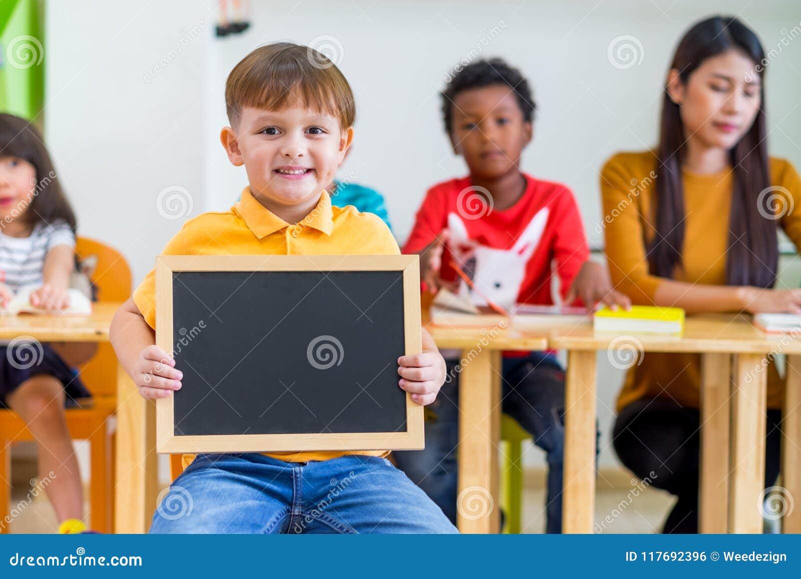 Scherzen Sie den Jungen, der Tafel mit zurück zu Schulwort mit diversi hält
