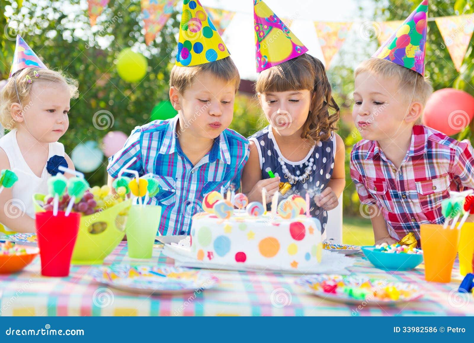 Scherzt Schlagkerzen auf Kuchen an der Geburtstagsfeier