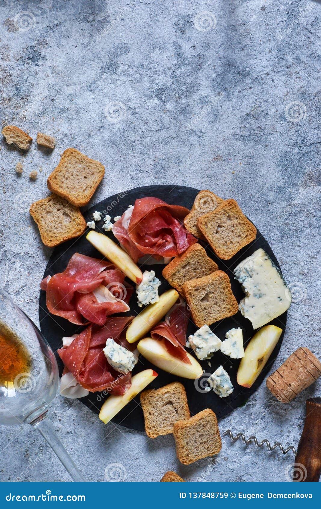 Schieferplatte mit Zartheit: jamon, Blauschimmelkäse, Briekäse und ein Glas rosafarbener Wein