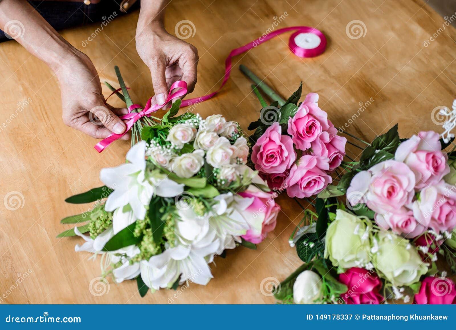Schikkend kunstbloemen bekleed decoratie thuis, het Jonge werk die van de vrouwenbloemist het organiseren van diy kunstbloem, amb