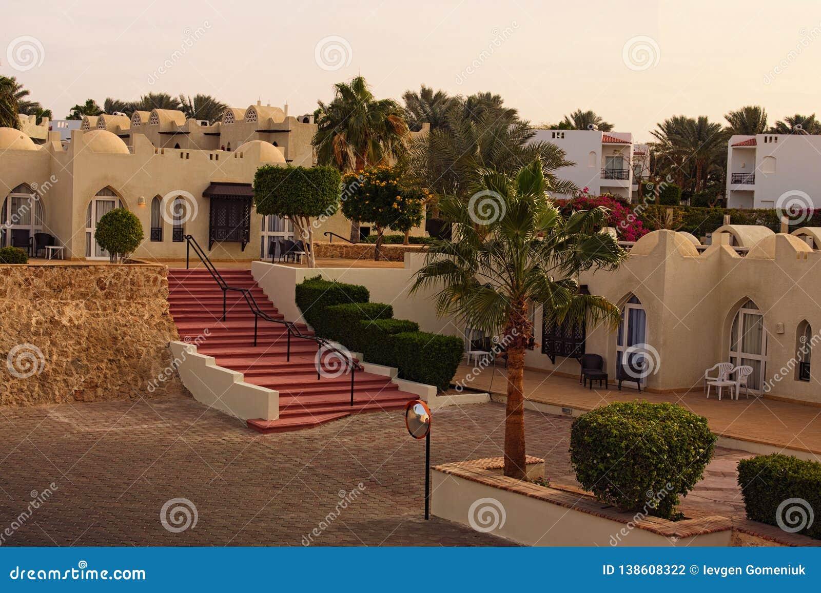 Schilderachtige ochtendmening van hotel de bouw van toevlucht met palmen en struiken tijdens zonsopgang Grsjeik van Sharm, Egypte