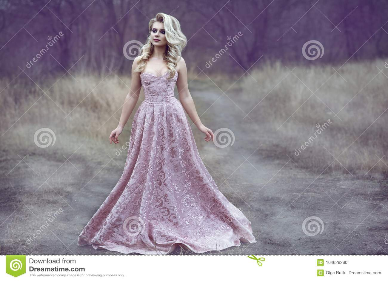 Schitterende blonde dame die met luxuriant kapsel in lange brokaatkleding langs de smalle weg in het hout lopen