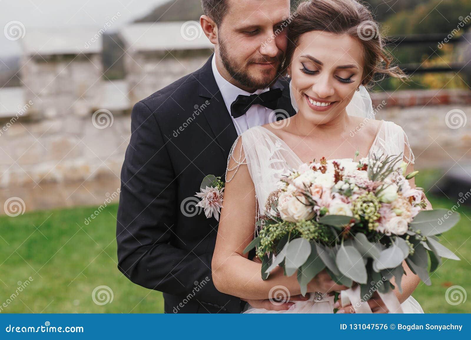 Schitterende bruid met modern boeket en modieuze bruidegom zacht hugg