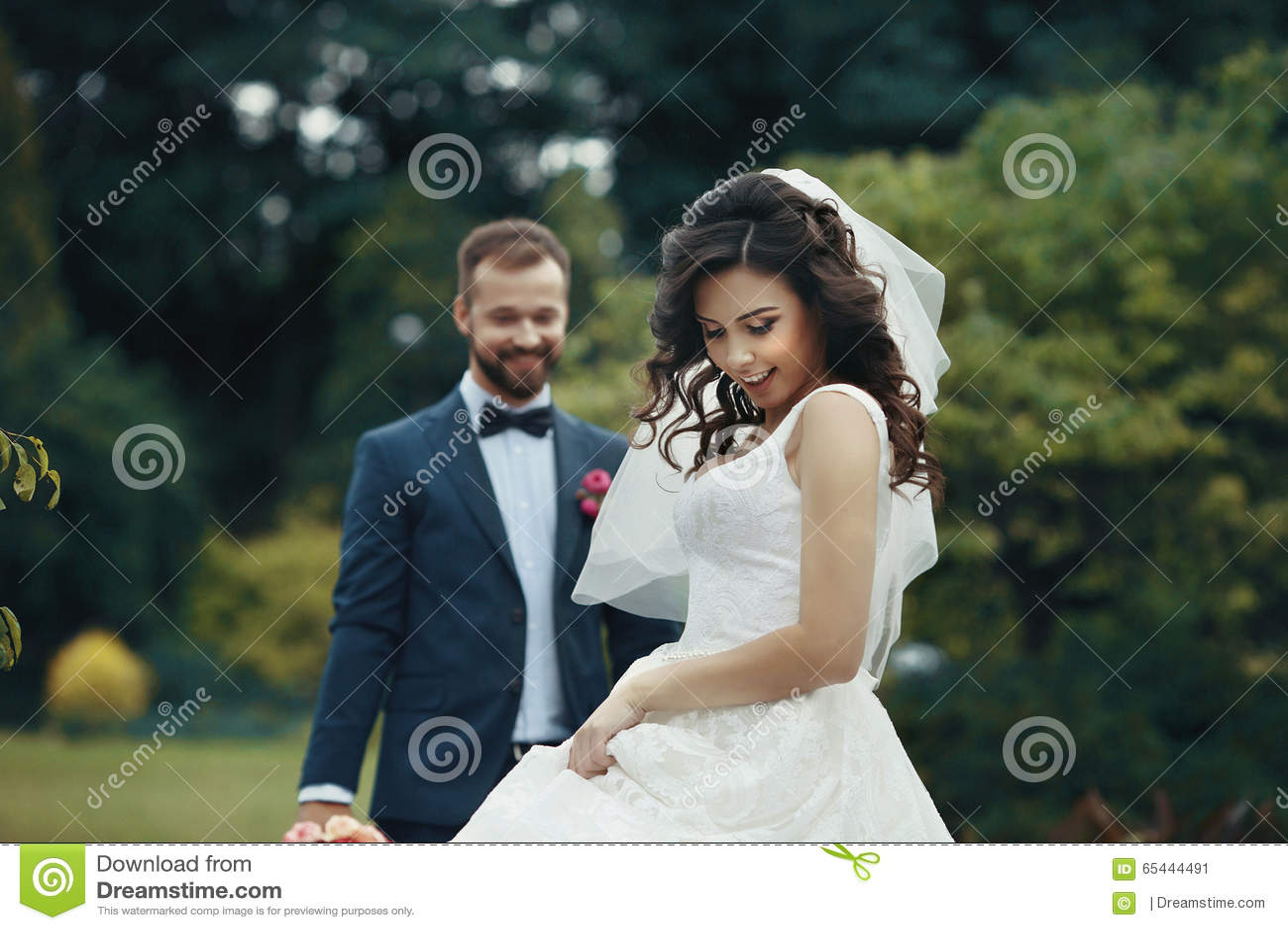 Schitterende donkerbruine bruid in het elegante kleding stellen in het park met