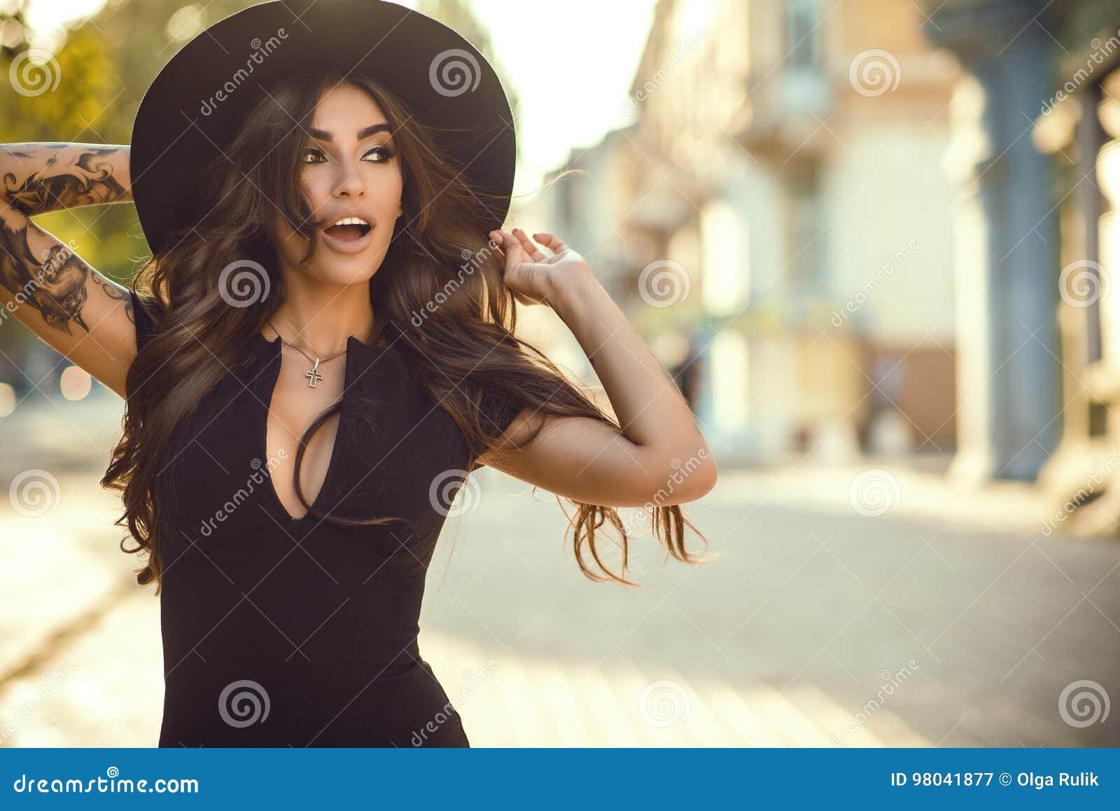 Schitterende glam tatoeeerde dame die haar in fedorahoed voor het houden weg te blazen niet, haar mond open met verrassing
