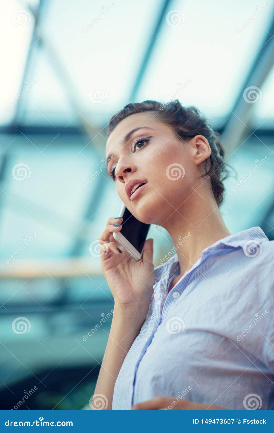 Schitterende vrouw die op mobiele telefoon bij luchthaven spreken