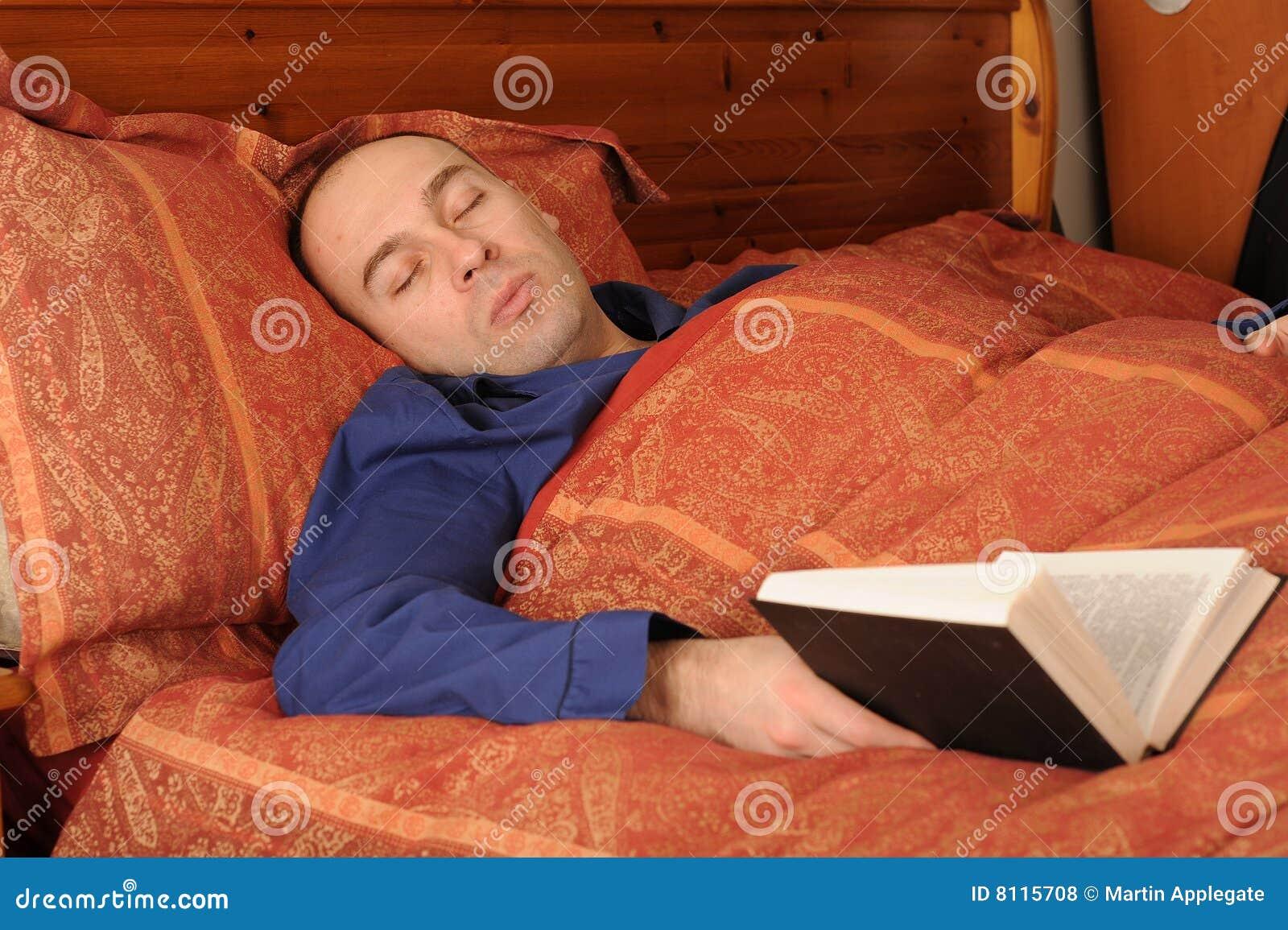 Ein von mittlerem alter mann gefallenes schlafendes im bett beim lesen