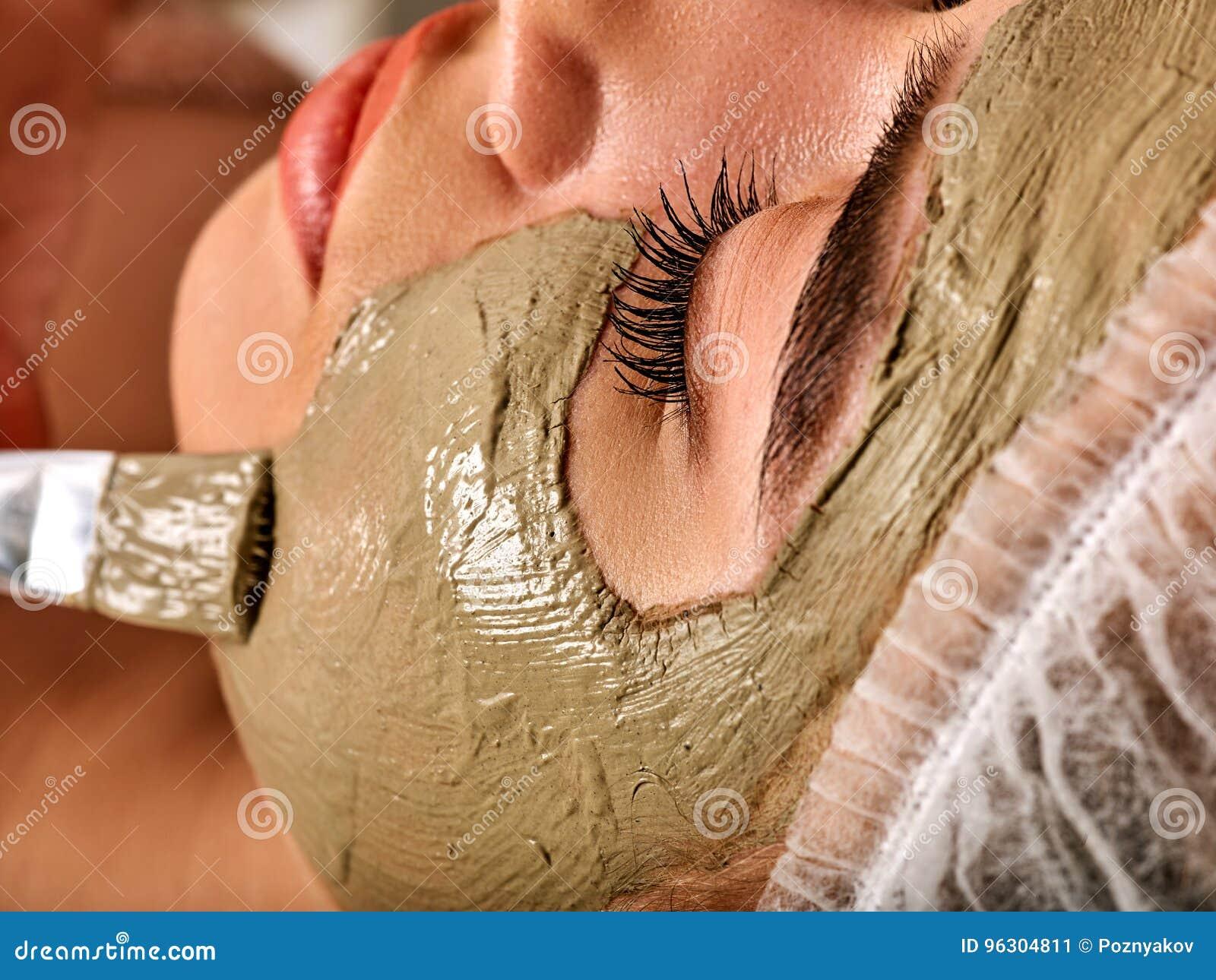 Schlammgesichtsmaske der Frau im Badekurortsalon Massage mit vollem Gesicht des Lehms