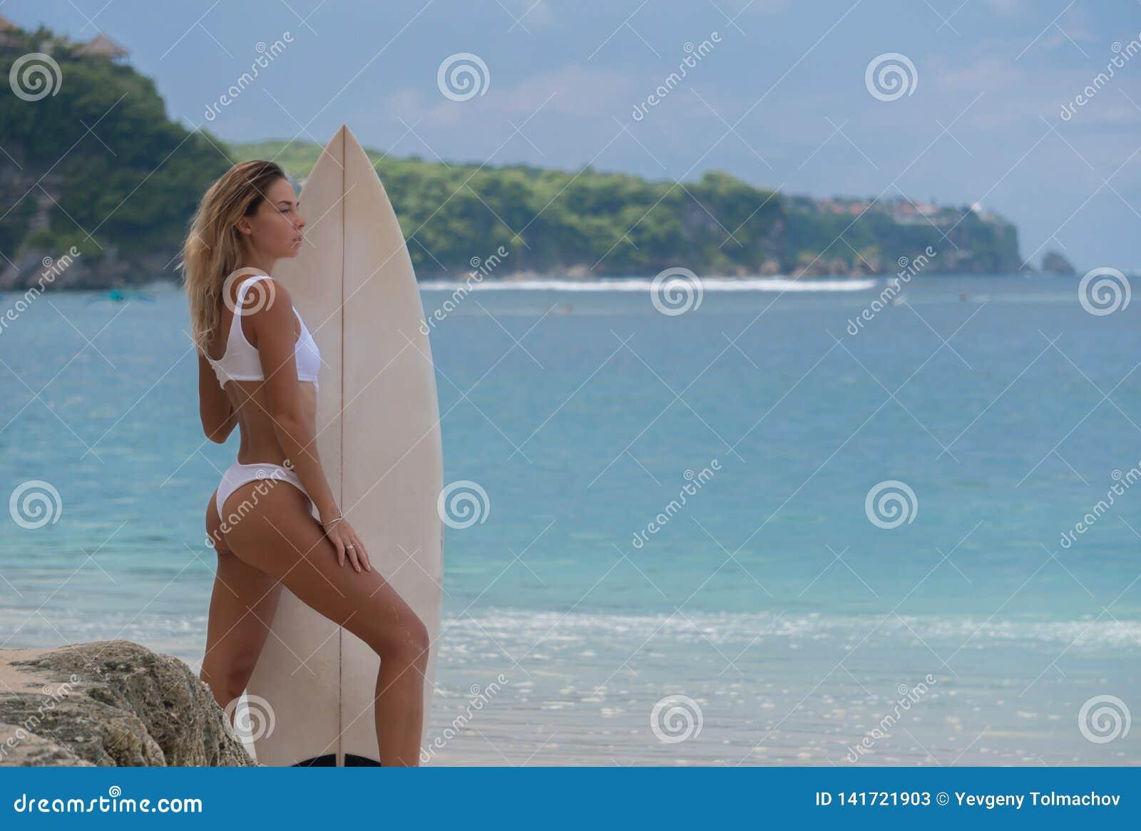 Schlanke junge Frau steht seitlich zur Kamera, das Holdingbrett, bereit zu surfen