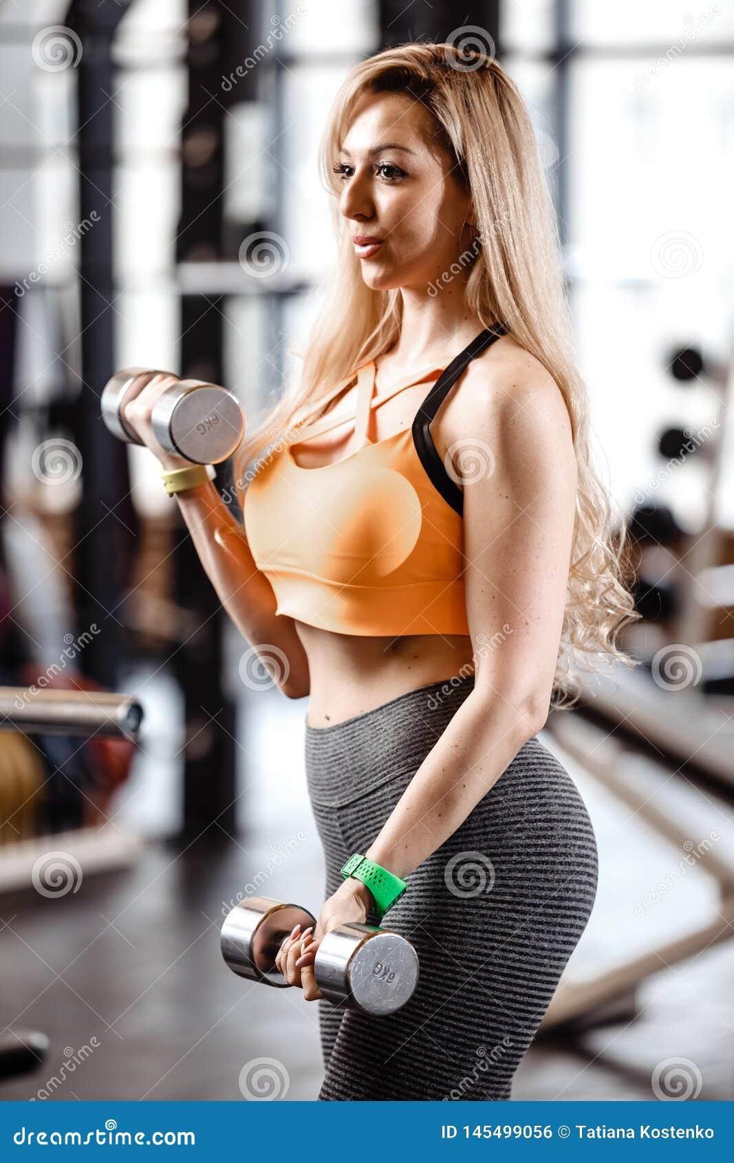 Schlankes blondes Mädchen mit dem langen Haar, das in einer Sportkleidung gekleidet wird, tut Übungen mit Dummköpfen in der moder