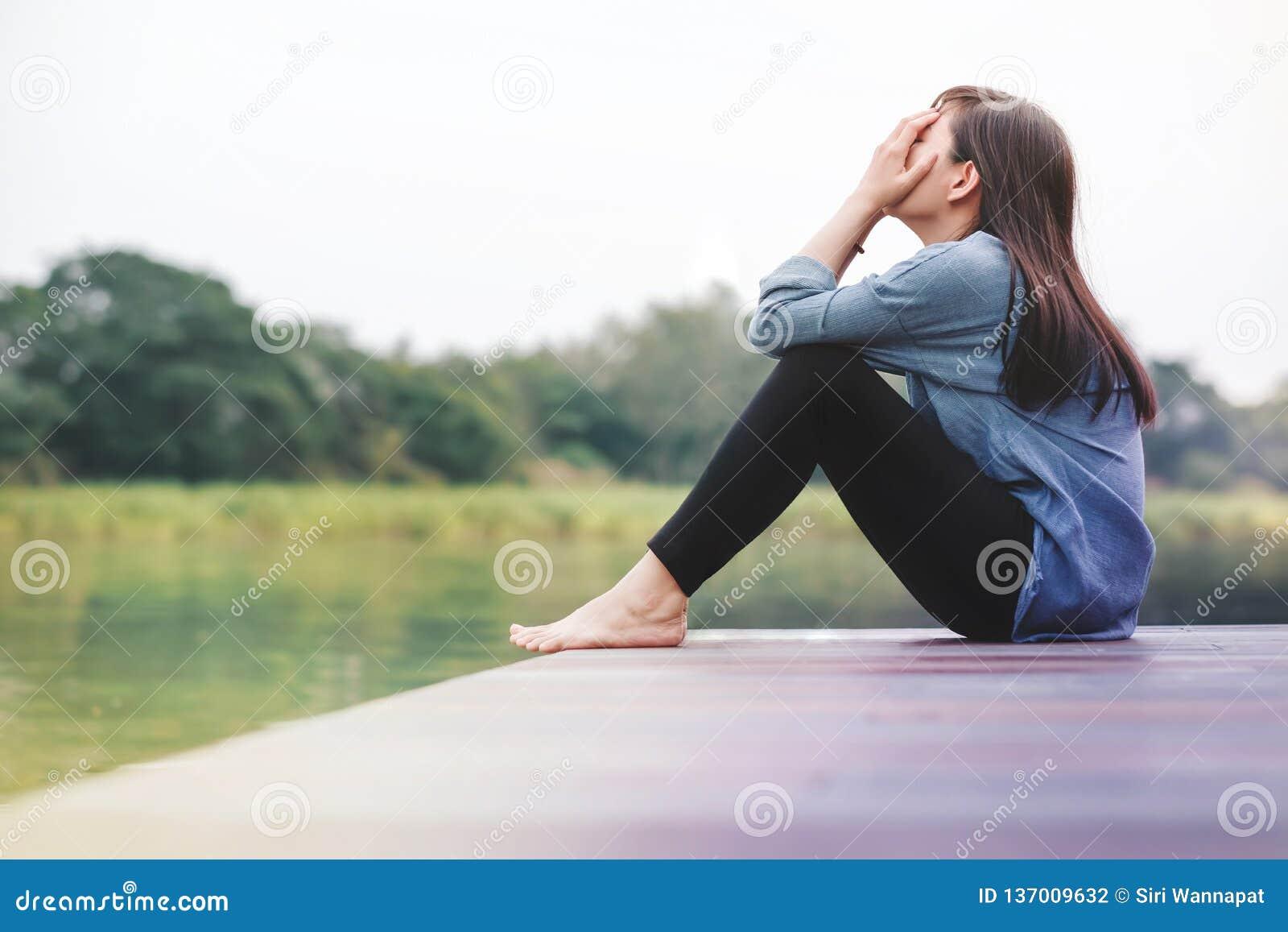 Schlechtes Tageskonzept Traurigkeits-Frau, die durch den Fluss sitzt