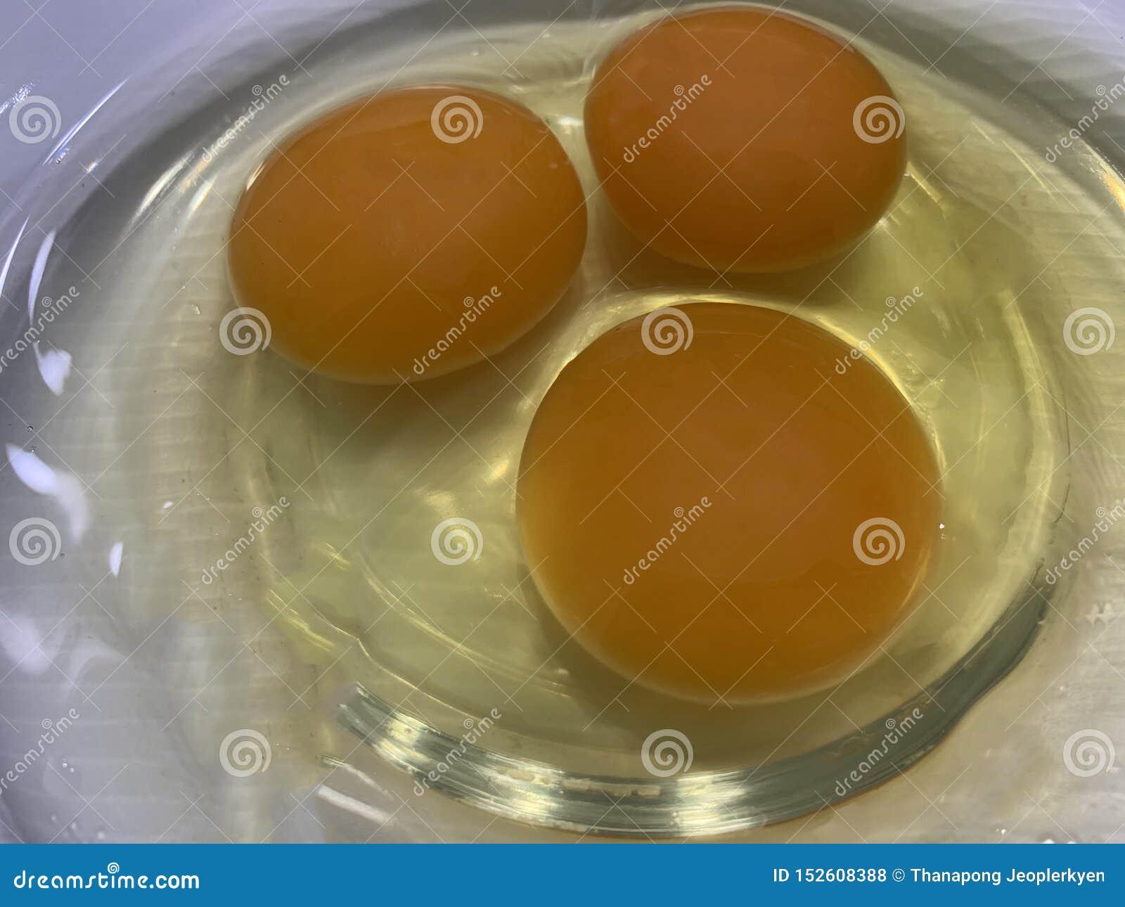 Schließen Sie herauf das Brechen des rohen Eies in der Schüsselanzeige