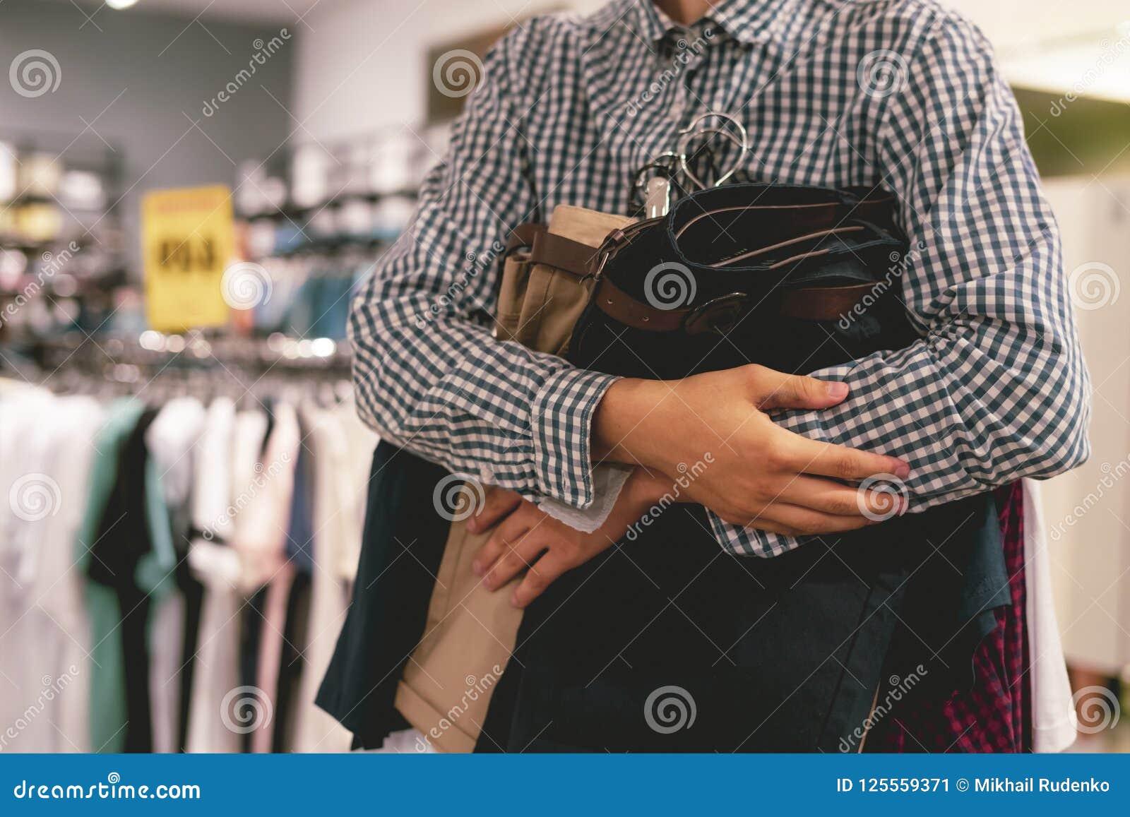 Schließen Sie herauf die Hand, die Bündel neue Kleidung hält, um im Speicher, ein Einkaufsverkaufskonzept zu kaufen