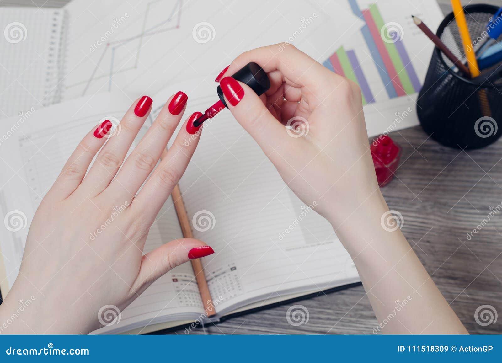 Schließen Sie herauf Foto von Frau ` s Händen, die Nägel über Desktopesprit malen
