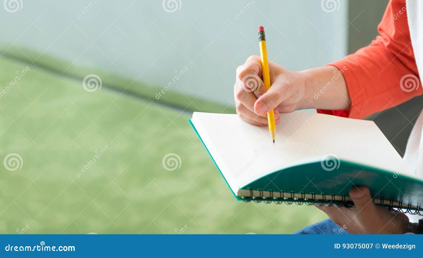 Schließen Sie herauf Hand des männlichen Jugendlichschreibens mit Bleistift auf Notizbuch a