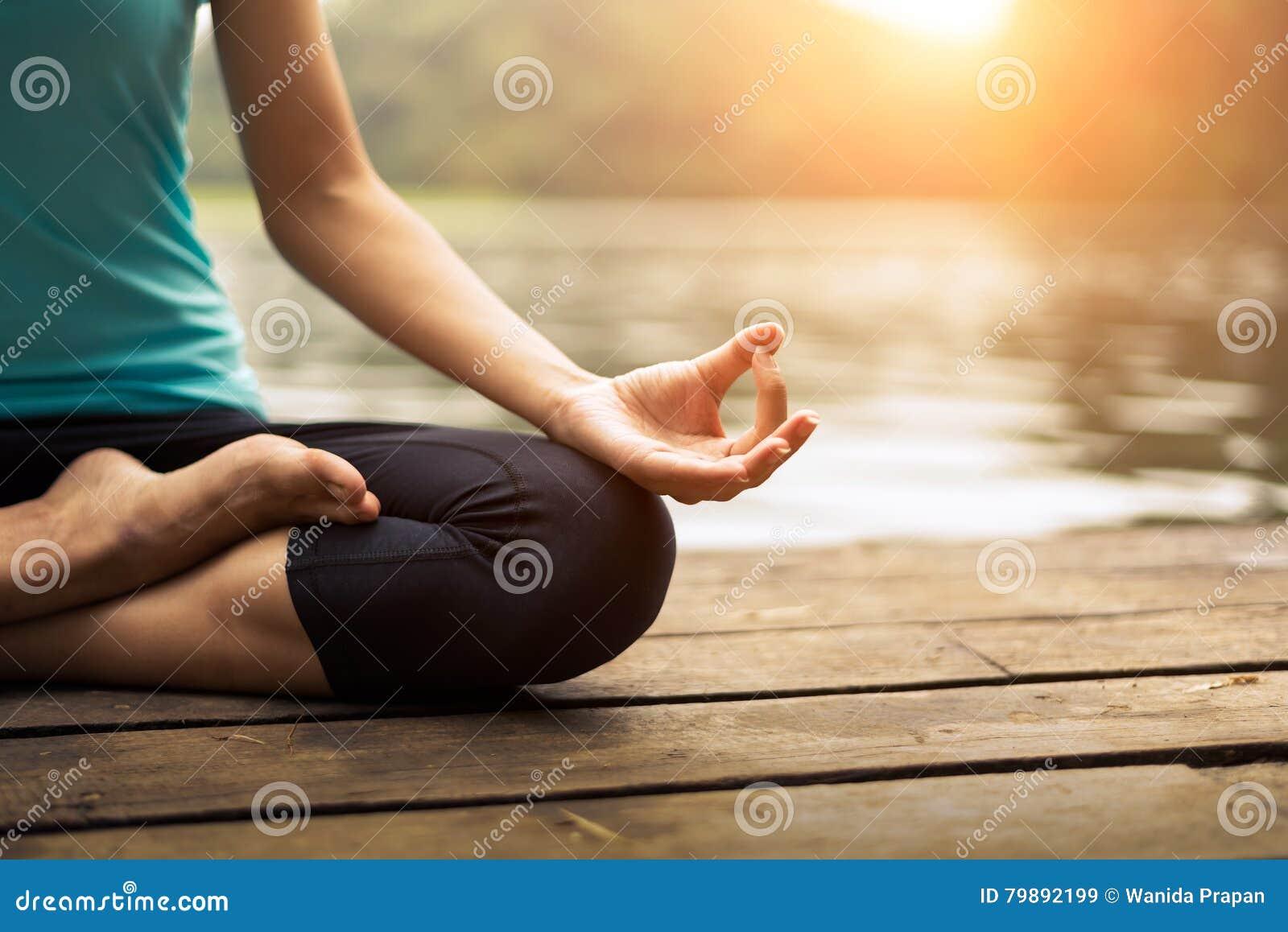 Schließen Sie herauf Hand Frau tun yoda das im Freien Frau, die Yoga am Naturhintergrund ausübt