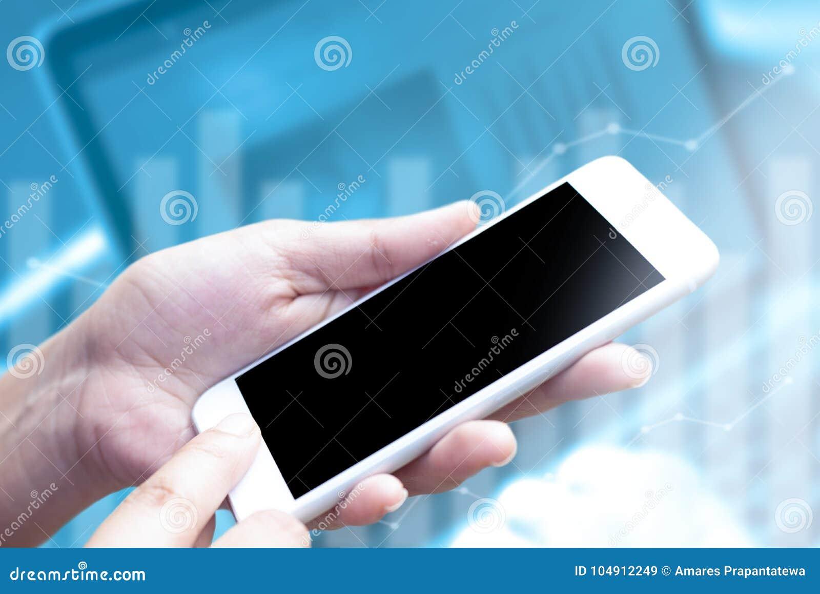 Schließen Sie herauf Hand unter Verwendung des Handys mit leerer Anzeige auf dem verwischten Laptop- und Diagrammhintergrund Konz