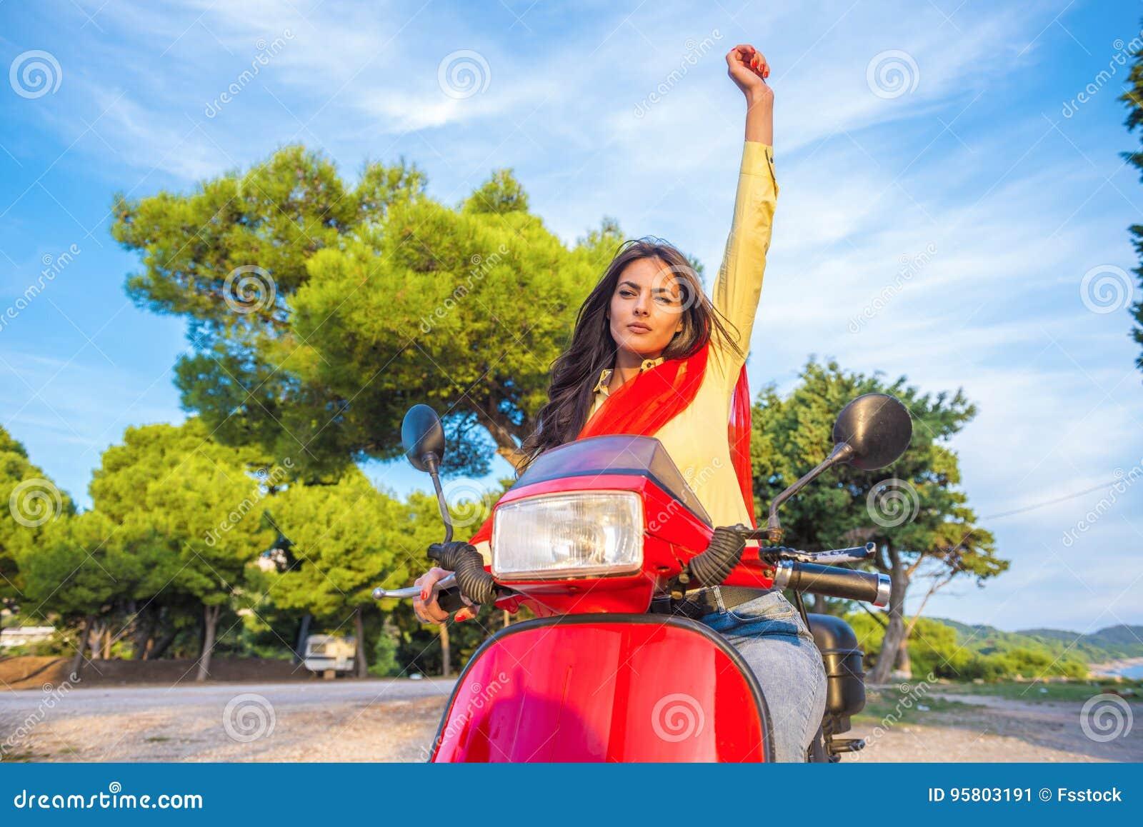 Schließen Sie herauf Lebensstilbild der jungen modernen Frau in der zufälligen Ausstattung, die auf Roller auf der Straße sitzt