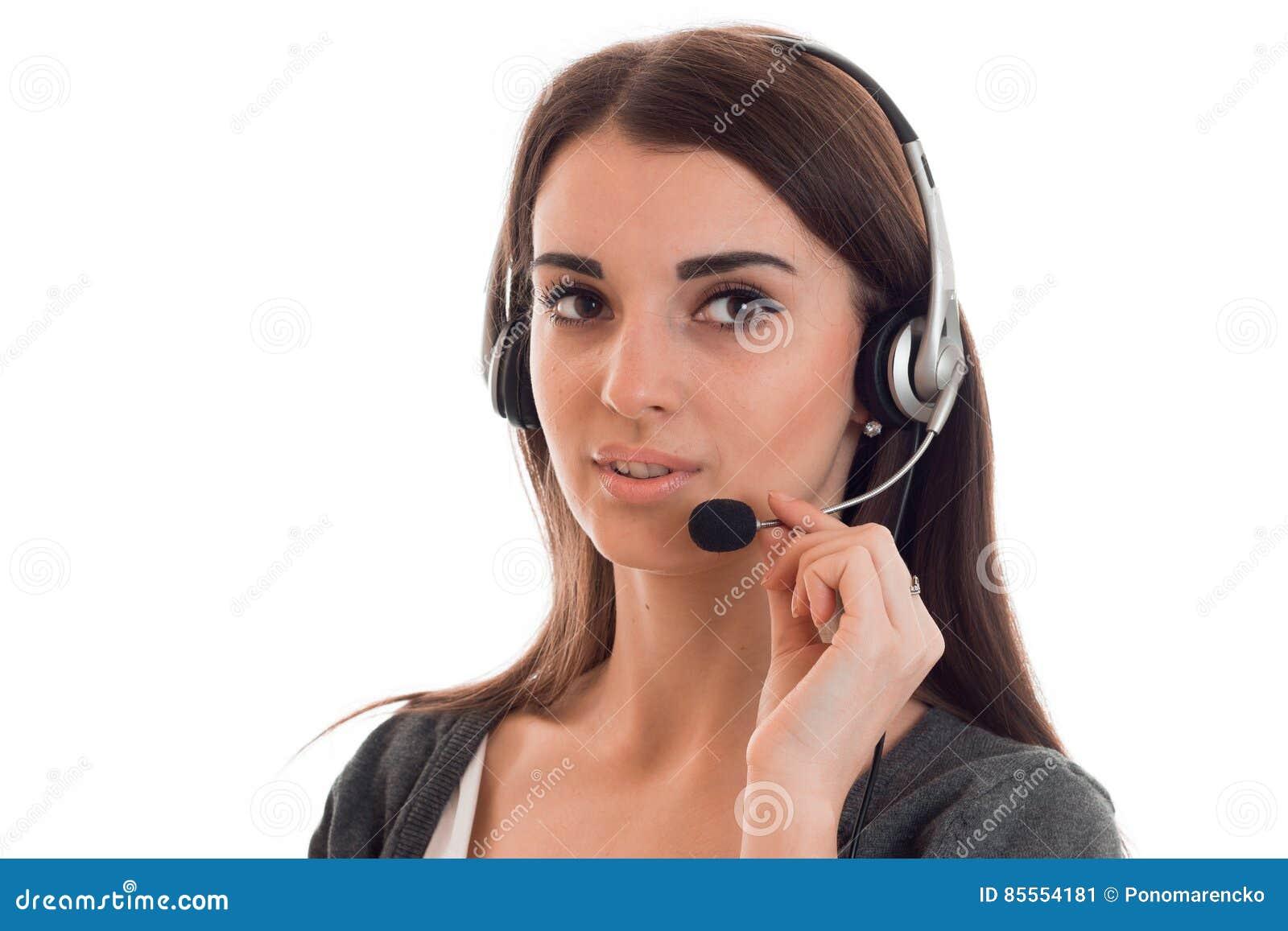 Schließen Sie herauf Porträt des jungen SchönheitsFernsprechamtmädchens mit den Kopfhörern, die auf weißem Hintergrund im Studio