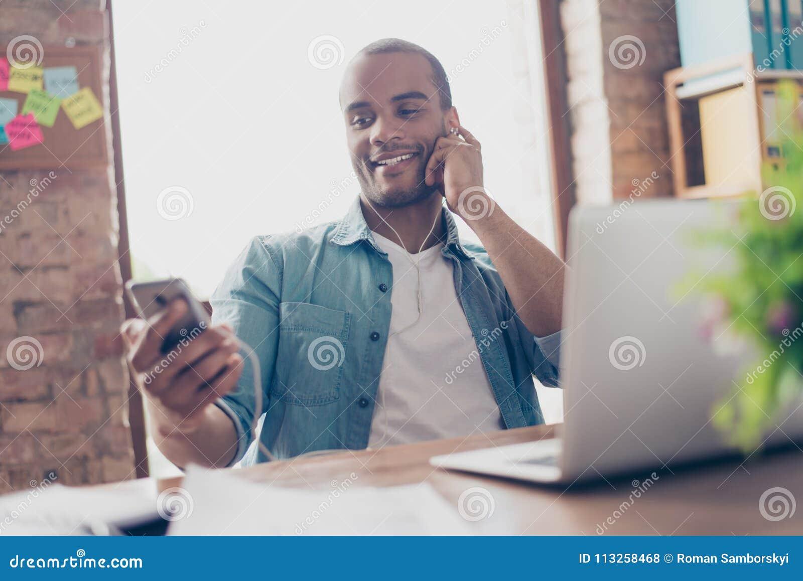 Schließen Sie herauf Porträt des netten jungen Afrokerls, der das Hören auf nettes Lied an seinem Arbeitsplatz, an seinem intelli