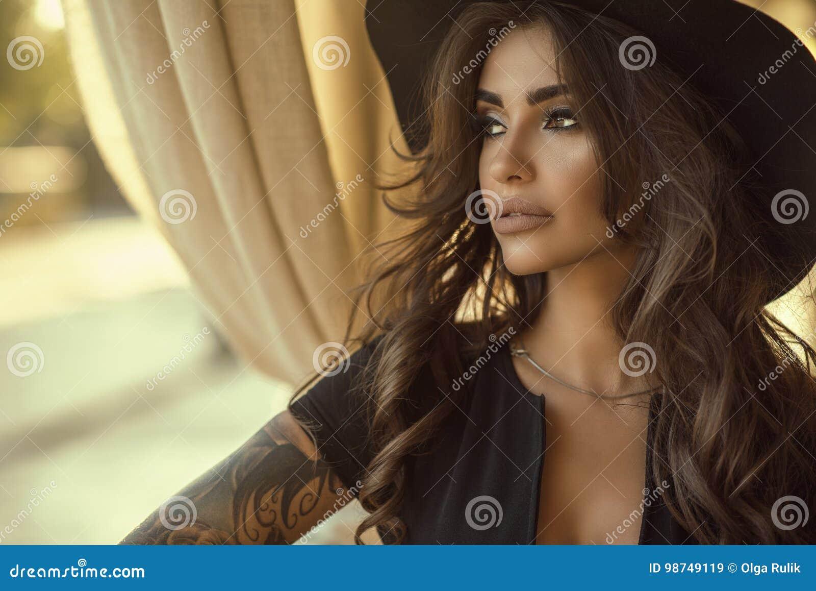 Schließen Sie herauf Porträt des schönen gebräunten Zauber tätowierten Modells mit dem langen gewellten Haar, das schwarzes Kleid