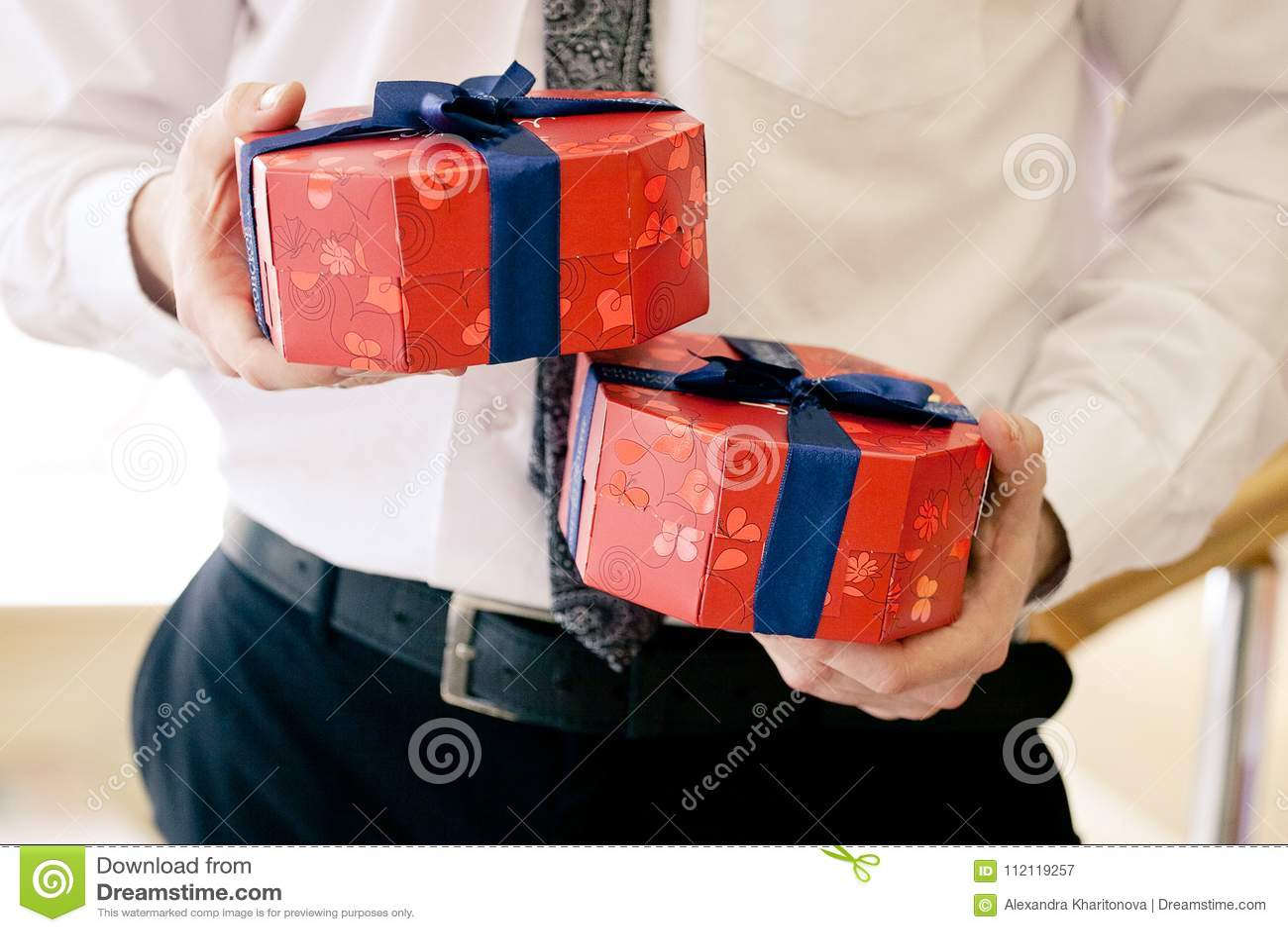 Schließen Sie herauf Schuss von den Geschäftsmannhänden, die helle Geschenkboxen eingewickelt mit blauem Band halten Weihnachten,