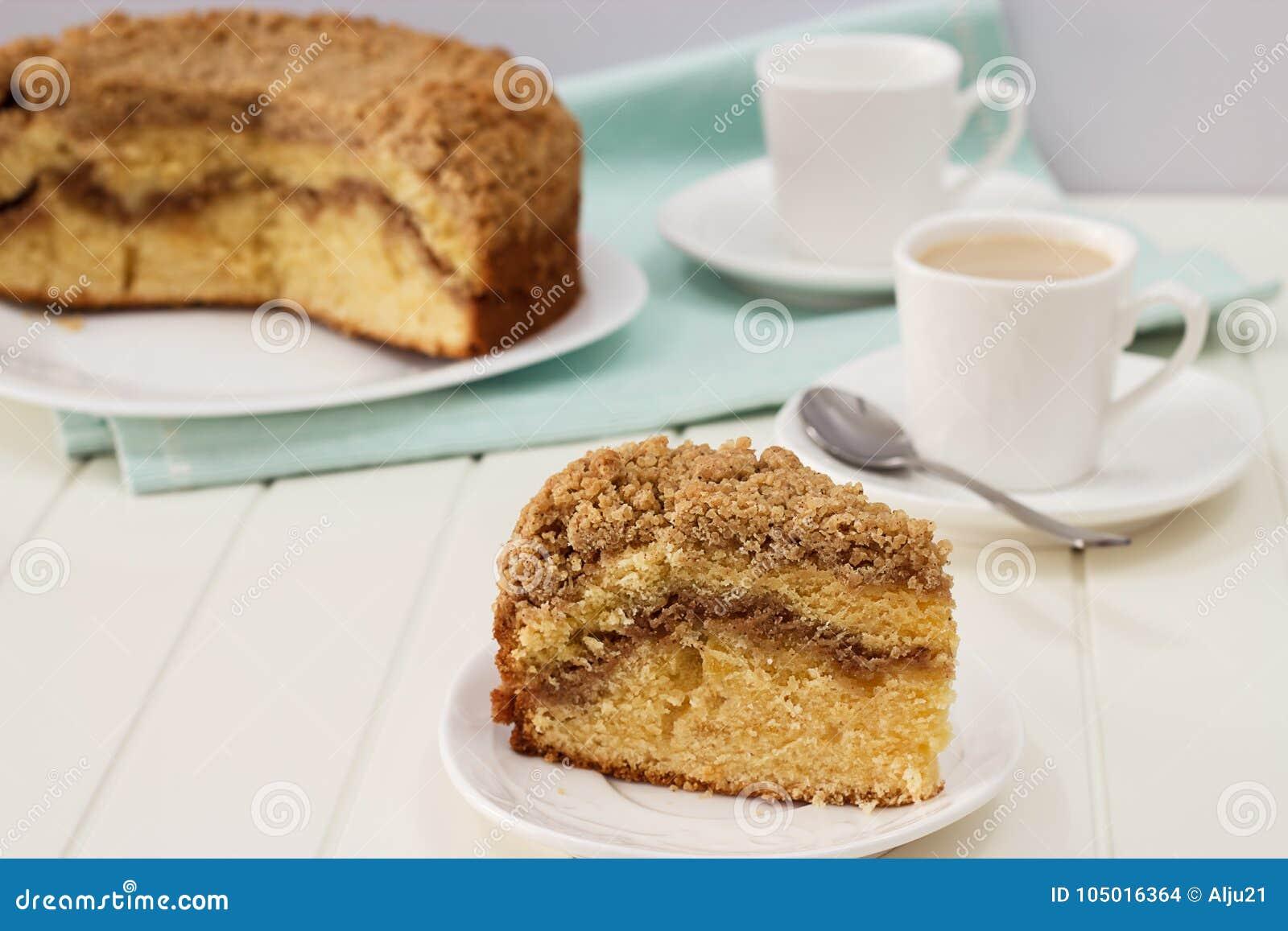 Schließen Sie herauf Stück des selbst gemachten Zimtkrümel-Kaffeekuchens und der Schale Milchtees