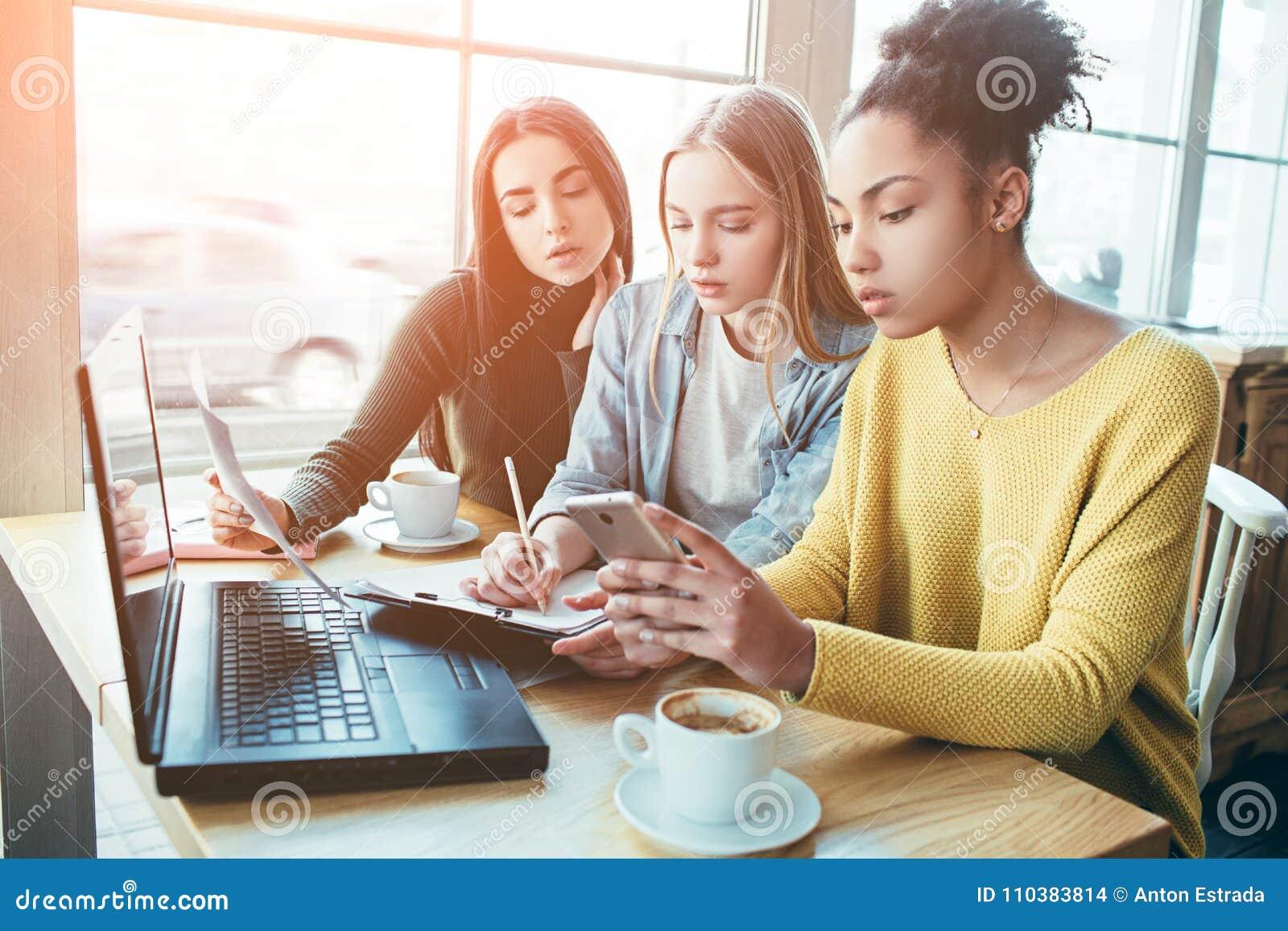 Schließen Sie oben und schneiden Sie Ansicht von drei Mädchen, die zusammen sitzen und das Diagramm des nominaleinkommens studier