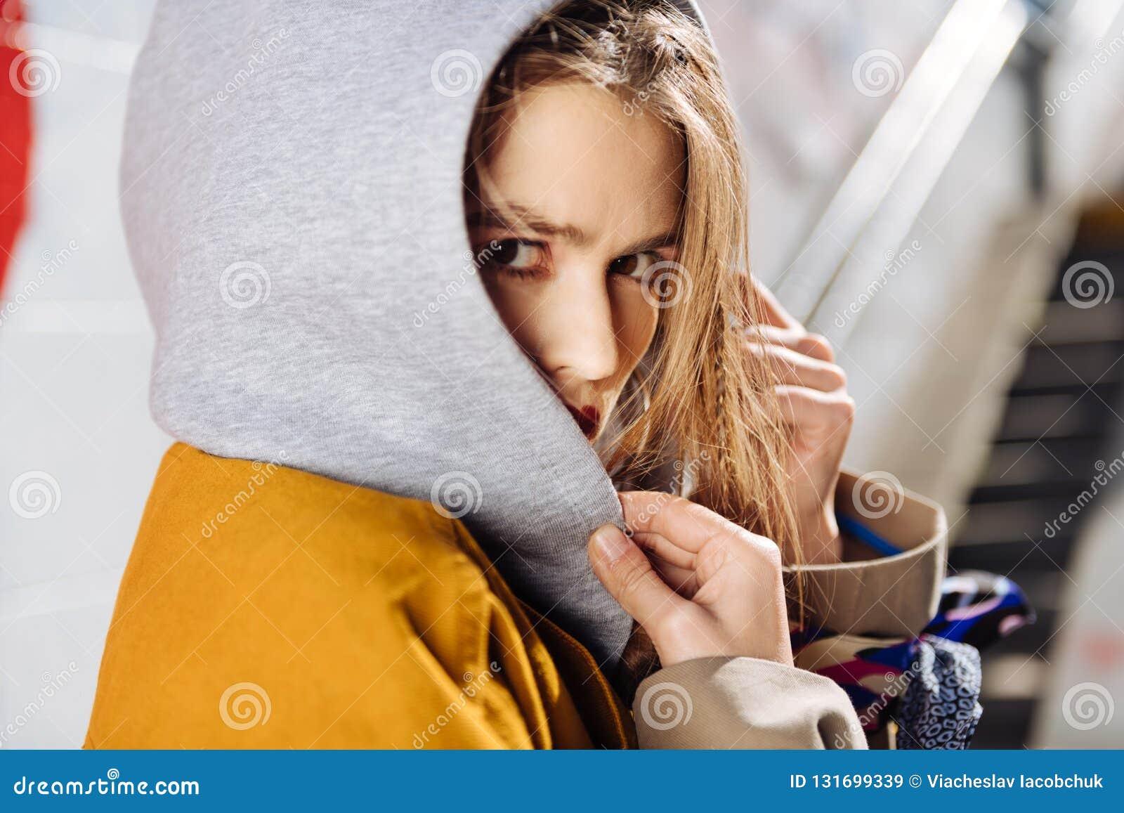 Schließen Sie oben vom ernsten dunkeläugigen Fotomodell, das grauen Hoodie trägt