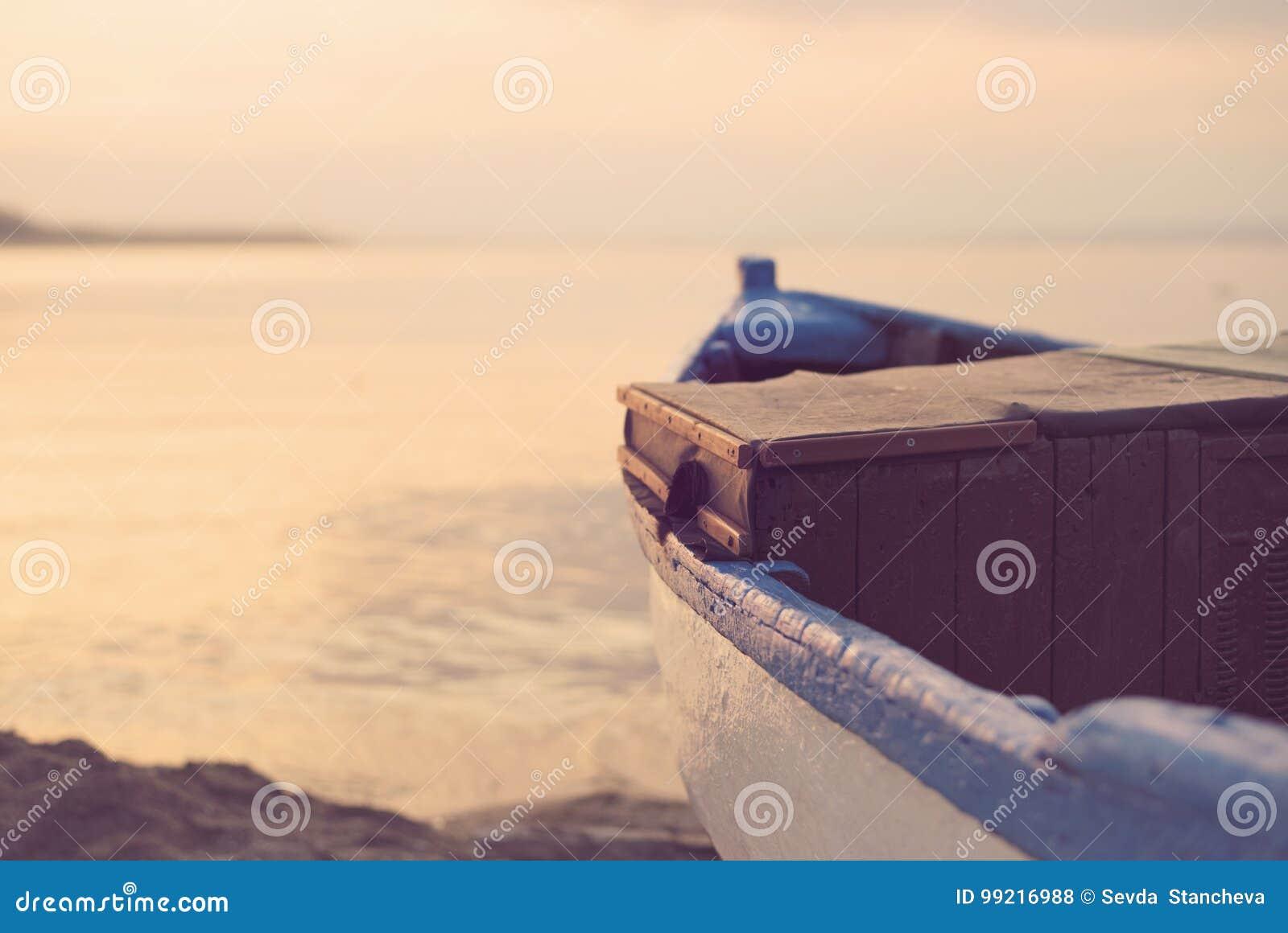 Schließen Sie oben vom hölzernen blauen Boot auf dem Strand Weinlese-Filter-Schauen