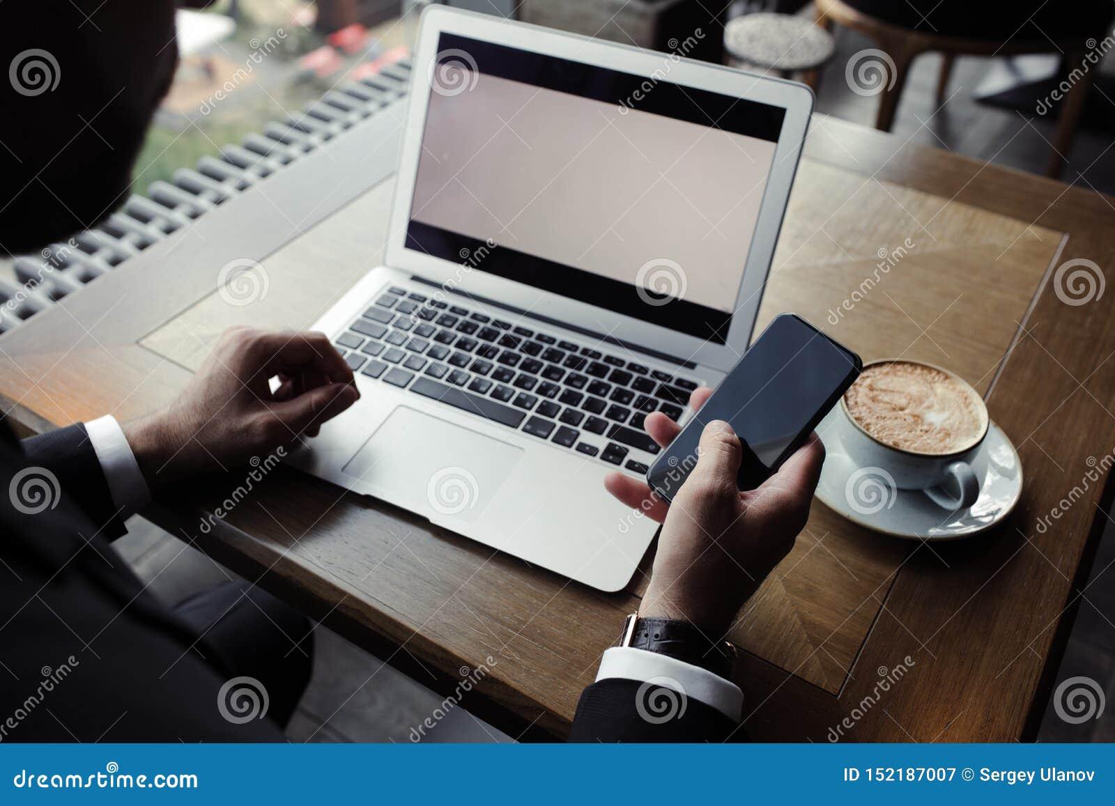 Schließen Sie oben vom hübschen Geschäftsmann und an Laptop im Restaurant arbeiten