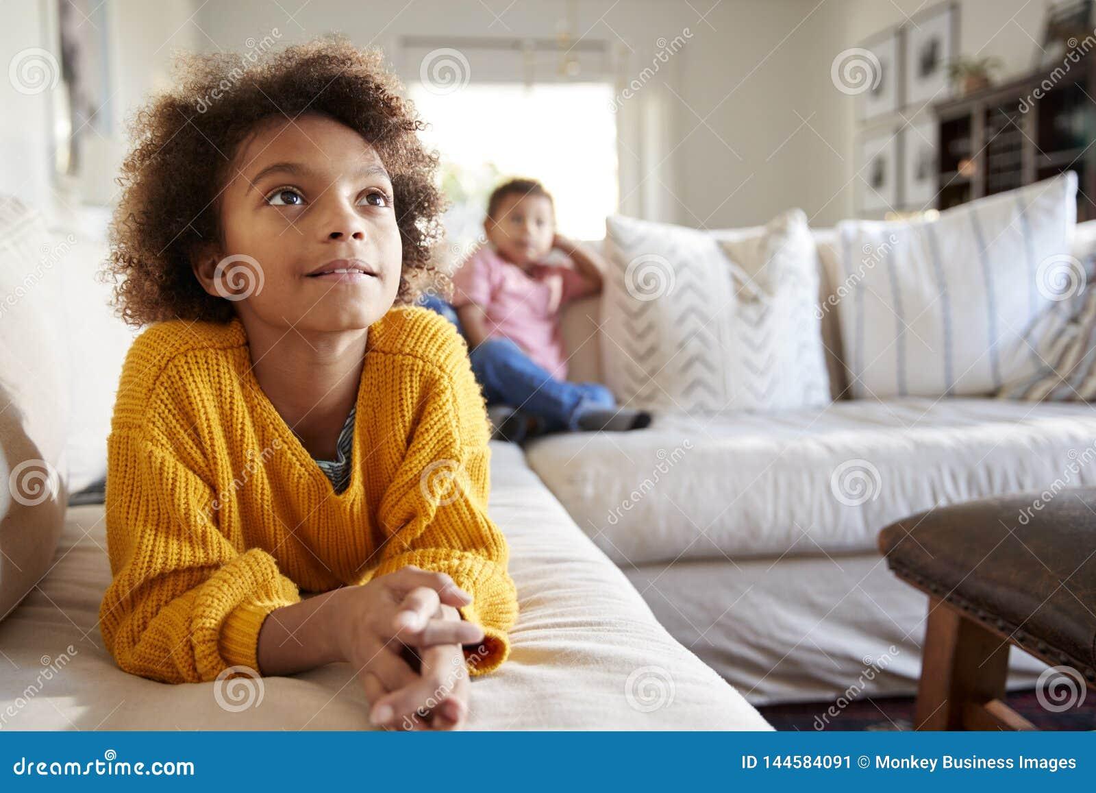 Schließen Sie oben vom jugendlichen Mädchen, das auf dem Sofa liegt, das im Wohnzimmer, ihr jüngerer Bruder fernsieht, der im Hin