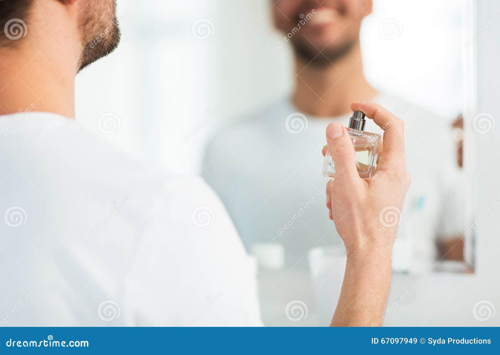 Schließen Sie oben vom Mann, der mit Parfüm am Badezimmer parfümiert