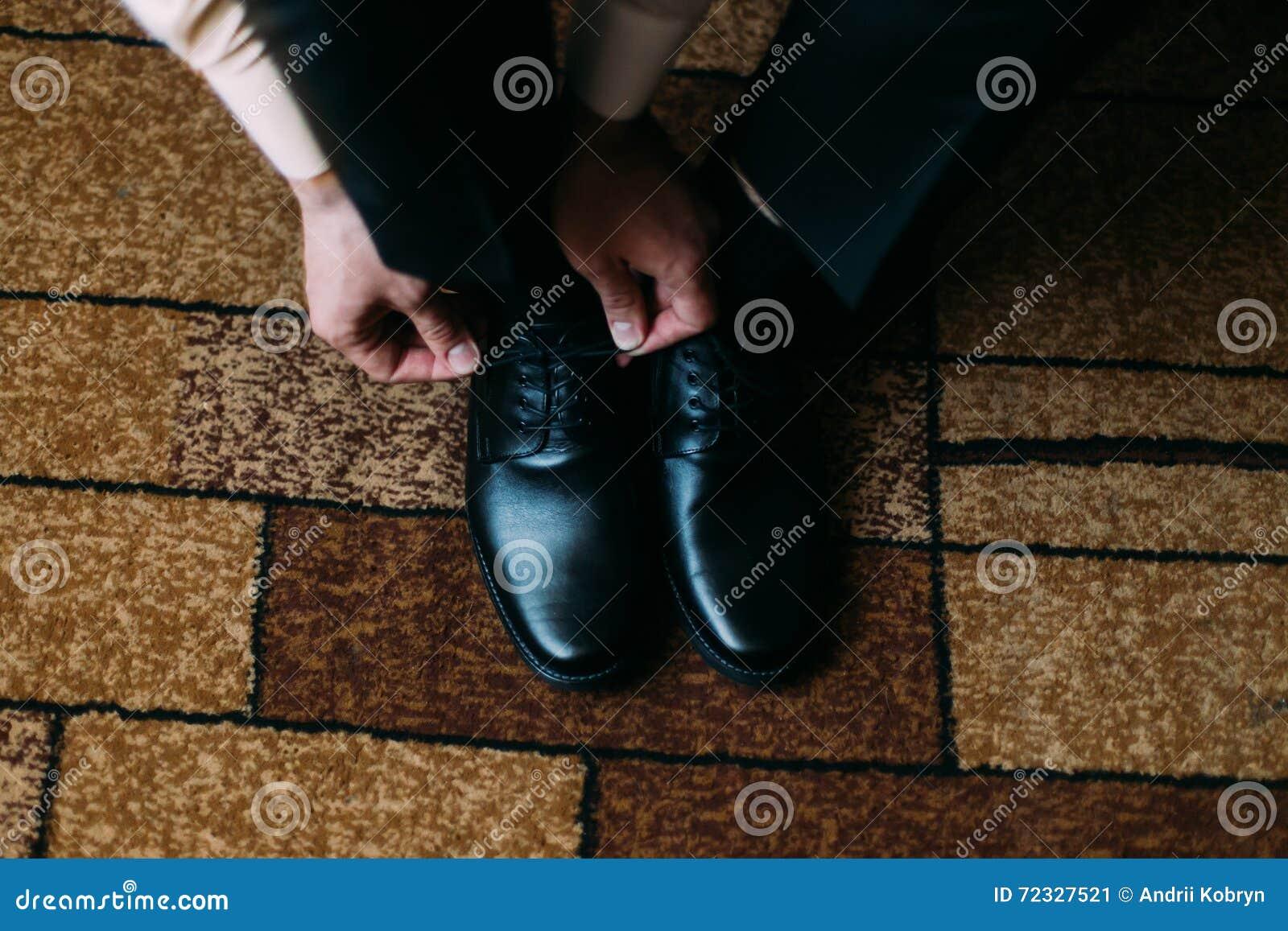 Schließen Sie oben vom Mannbein und -händen, welche die stilvollen schwarzen Schnürsenkel binden, die auf Teppich mit rechteckige