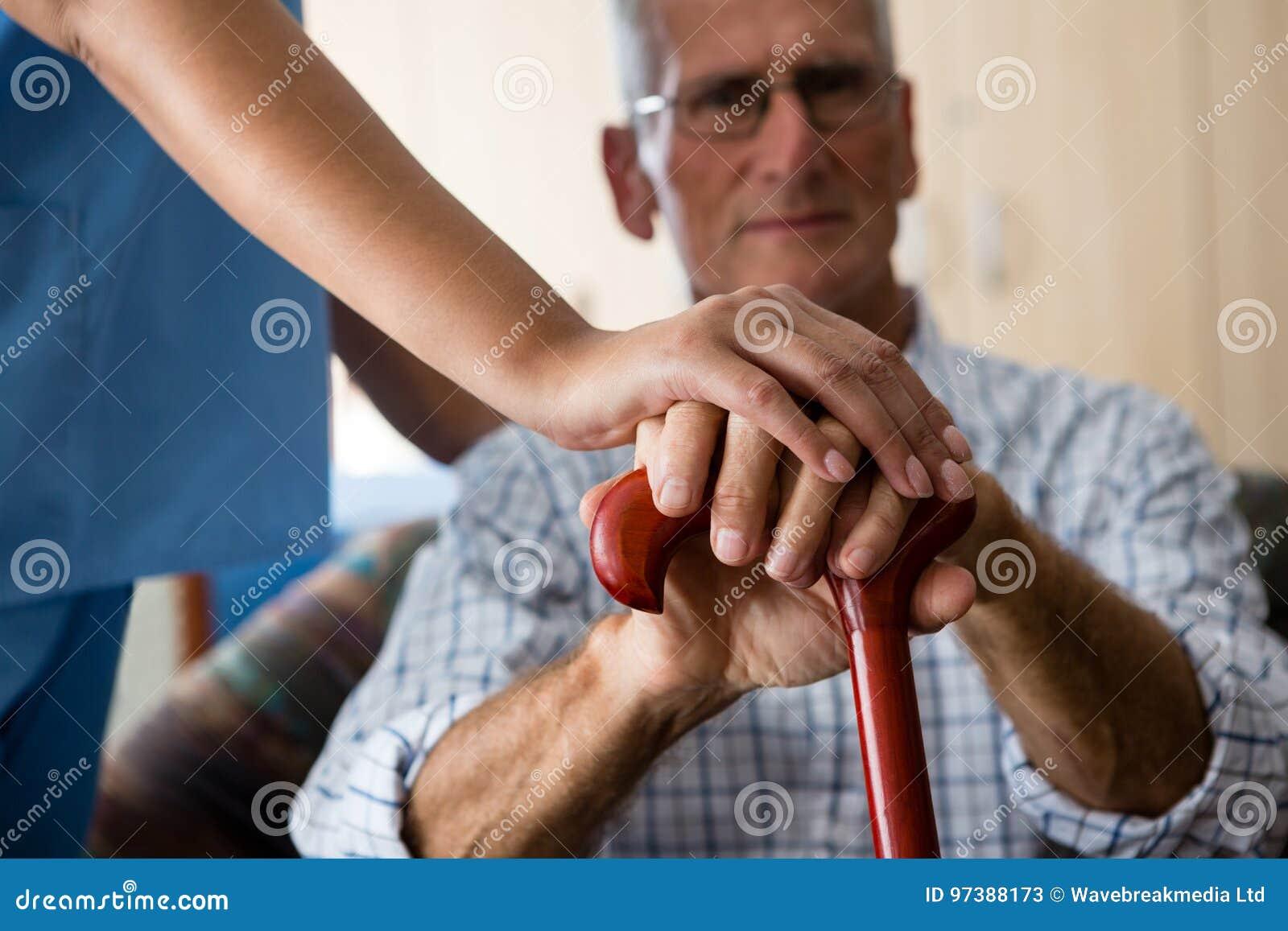 Schließen Sie oben von den Händen der Ärztin und des älteren Mannes, die gehenden Stock halten